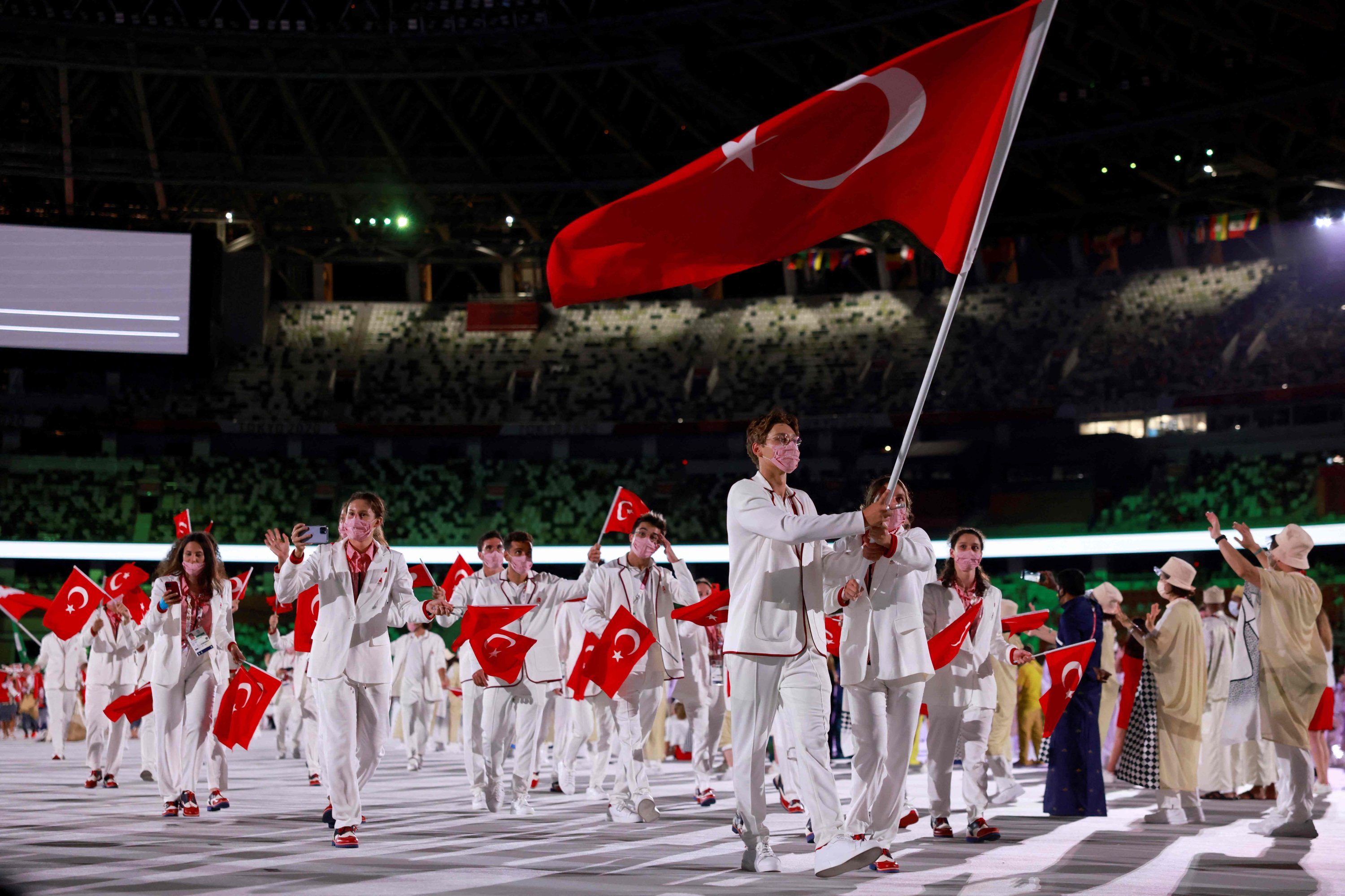 Turkey's flag bearer Berke Saka (L) and Merve Tuncel lead the Team Turkey during the opening ceremony in the Olympic Stadium at the 2020 Summer Olympics, in Tokyo, Japan, July 23, 2021. (AFP Photo)