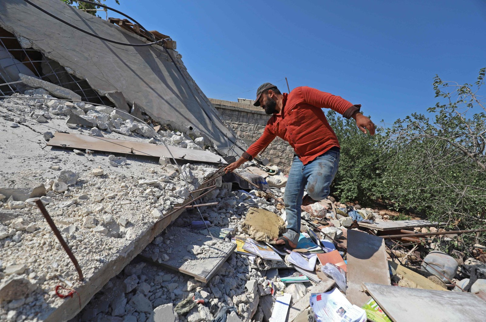 A Syrian man walks atop the ruins of a house, destroyed in a reported regime artillery shelling, in the village of Iblin in the Jabal al-Zawiya region of the opposition-held northwestern Idlib province, Syria, on July 22, 2021. (AFP Photo)