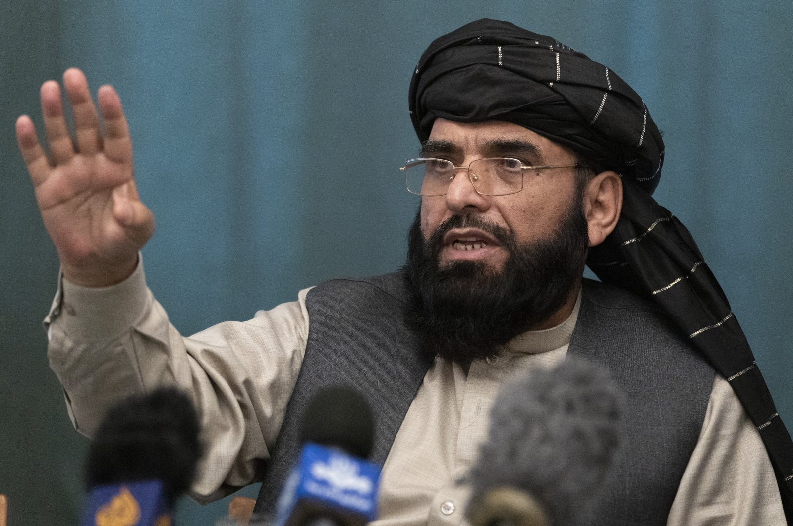 Suhail Shaheen, Afghan Taliban spokesperson and a member of the negotiation team gestures while speaking during a joint news conference in Moscow, Russia, March 19, 2021. (AP Photo)