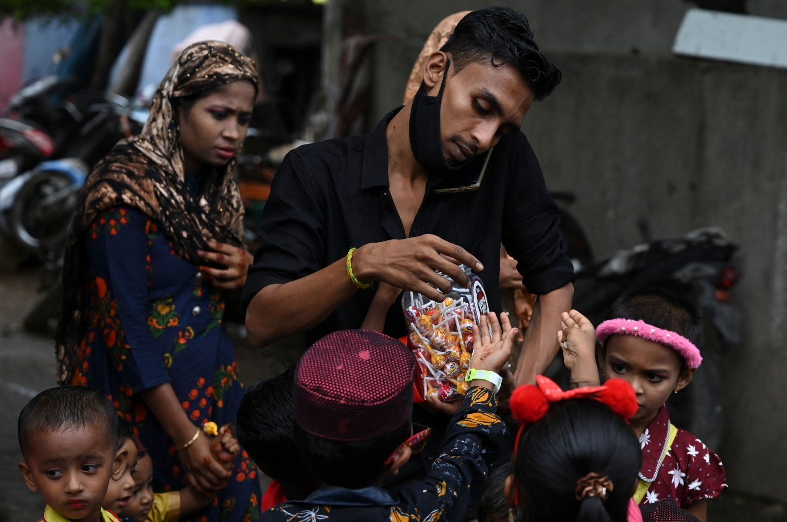 A Rohingya Muslim refugee (C) distributes candy to children during Eid al-Adha, or the Festival of Sacrifice, at a refugee camp on the outskirts of Chennai, India, on July 21, 2021. (AFP Photo)