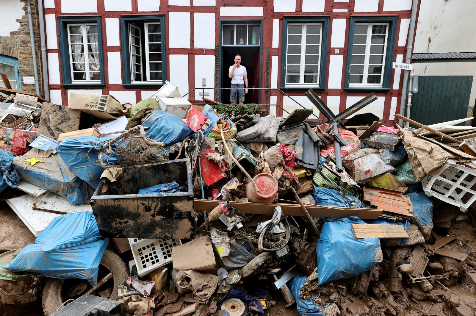 A man looks on outside a house in an area affected by floods caused by heavy rainfalls in Bad Muenstereifel, Germany, July 19, 2021. (Reuters Photo)