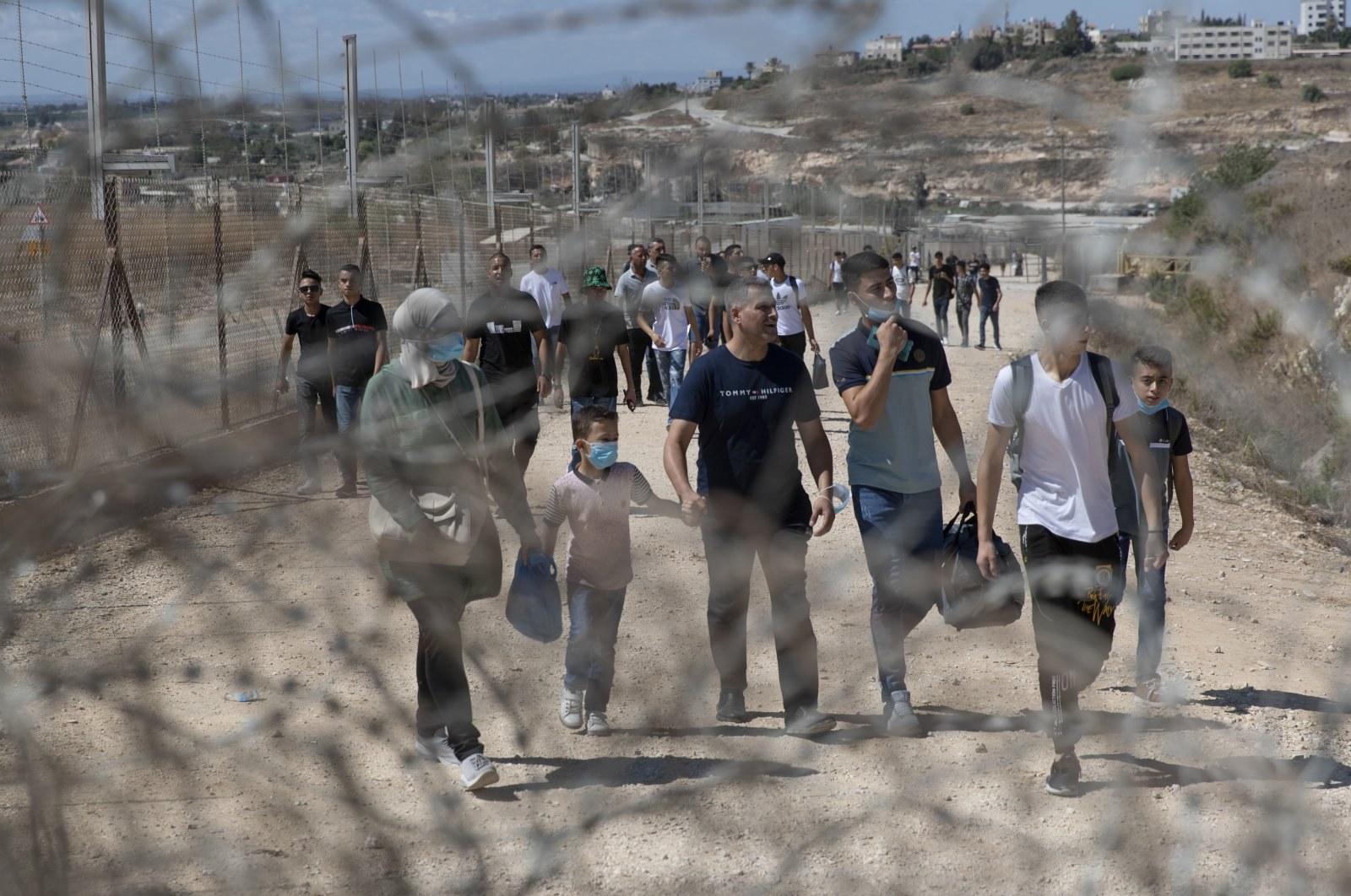 Palestinians cross into Israel through a damaged section in the Israeli separation fence, aiming for a day on the beach as they celebrate the second day of Eid al-Adha, in the West Bank village of Faroun, near Tulkarm, Palestine, July 21, 2021. (AP Photo)