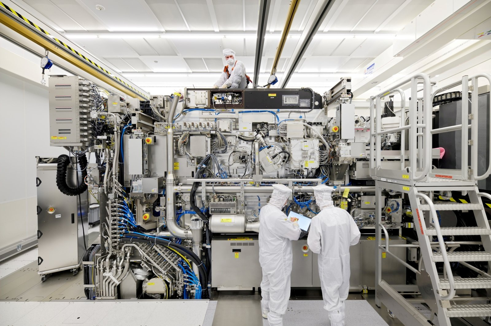 Employees are seen working on the final assembly of ASML's TWINSCAN NXE:3400B semiconductor lithography tool with its panels removed, in Veldhoven, Netherlands, April 4, 2019. (ASML via Reuters)