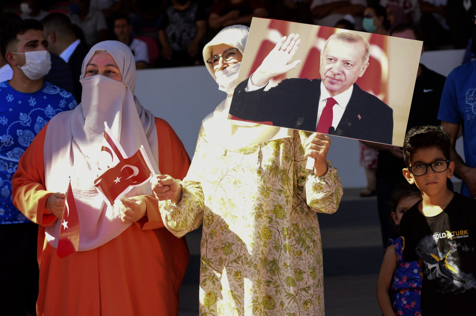 A Turkish woman (R) holds a portrait of Turkish President Recep Tayyip Erdoğan as another woman holds a Turkish flag during the military parade marking the Peace Operation that took place on July 20, 1974, in Lefkoşa (Nicosia), Turkish Cyprus, July 20, 2021. (AP Photo)