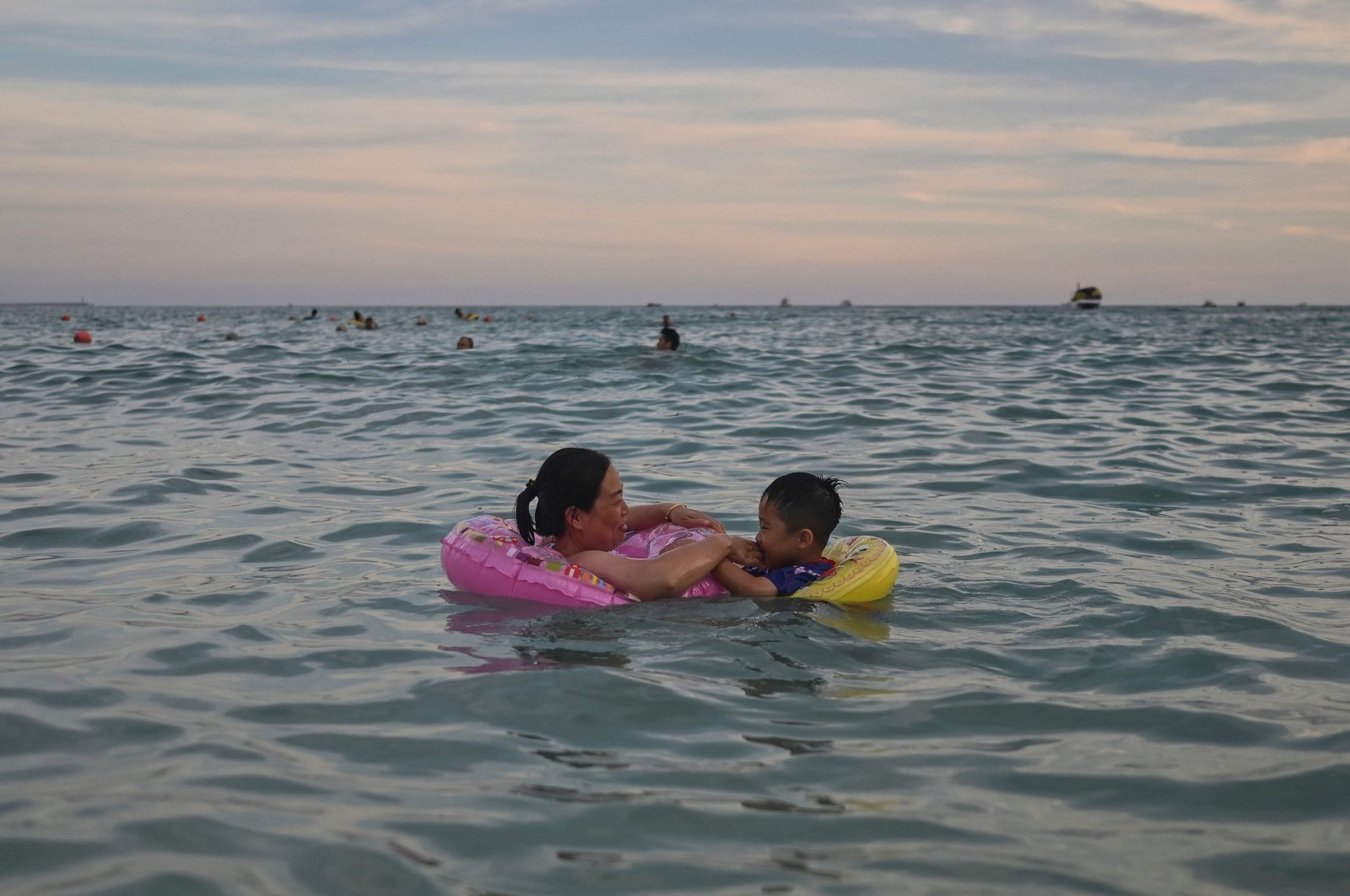 A woman and a child swim at Dadonghai beach in Sanya on China's tropical Hainan Island on July 18, 2021. (AFP Photo)