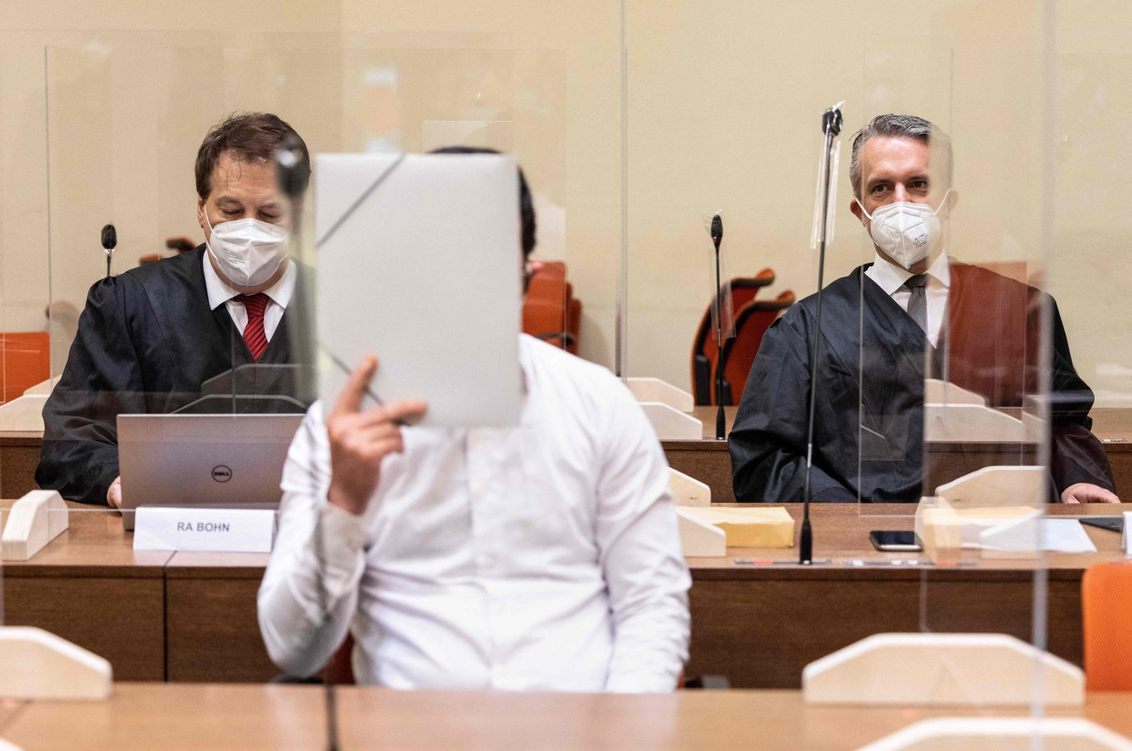Defendant Muharrem D. (C) covers his face before the start of his trial, Munich, Germany, July 23, 2021. (AFP PHOTO)