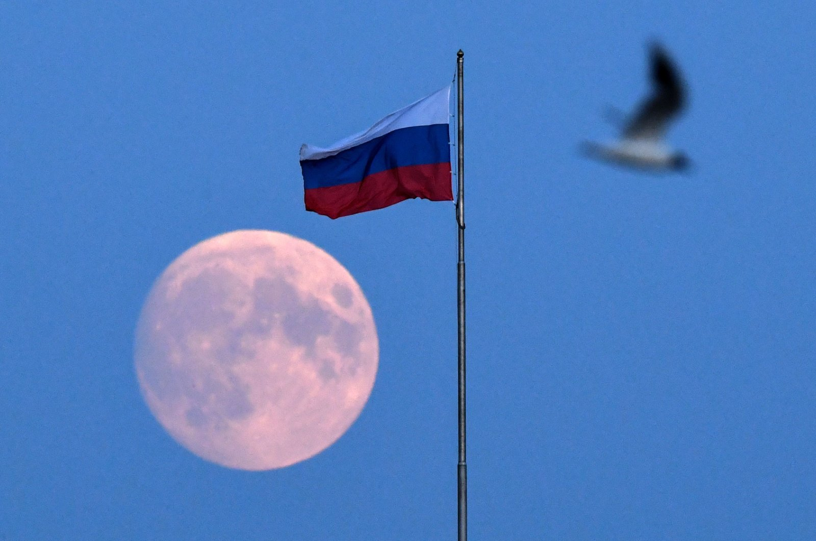 The full moon is photographed behind the Russian national flag in downtown Saint Petersburg, Russia, on June 23, 2021. (AFP Photo)