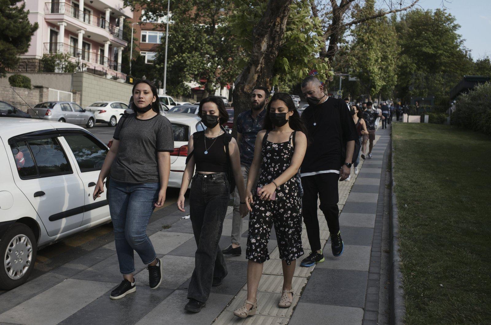 People wearing masks to help protect against the spread of coronavirus, walk along a street, in Ankara, Turkey, July 10, 2021. (AP Photo)