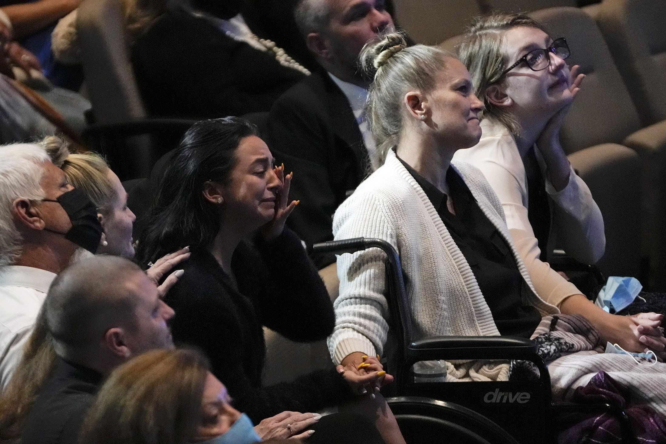 Angela Gonzalez (C-R), holds hands with her daughters Tayler Scheinhaus (C-L), and Deven Gonzalez (R), during the funeral service for their late husband and father Edgar Gonzalez, in Florida, U.S., July 23, 2021. (AP Photo)