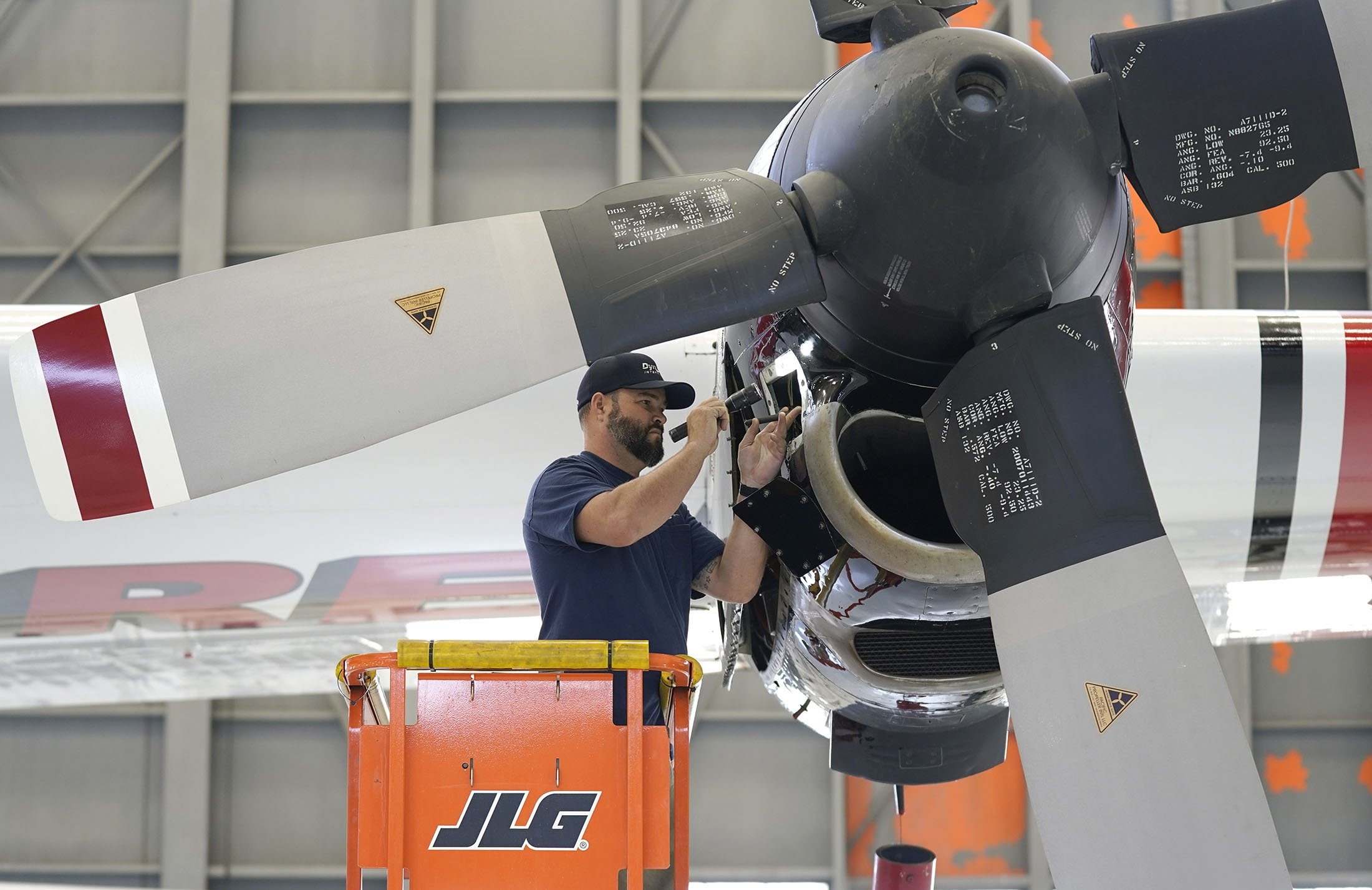 Aircraft Mechanic Cody Poole inspects one of the engines on a recently acquired C-130 aircraft, hangared at McClellan Airpark in Sacramento, California, U.S., July 23, 2021. (AP Photo)