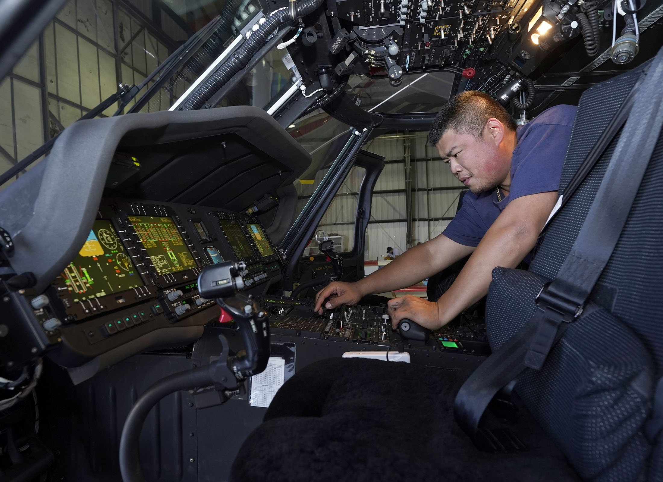 Avionics mechanic Mike Luong inspects the control panel of Sikorsky Firehawk helicopter at McClellan Airpark in Sacramento, California, U.S., July 23, 2021. (AP Photo)