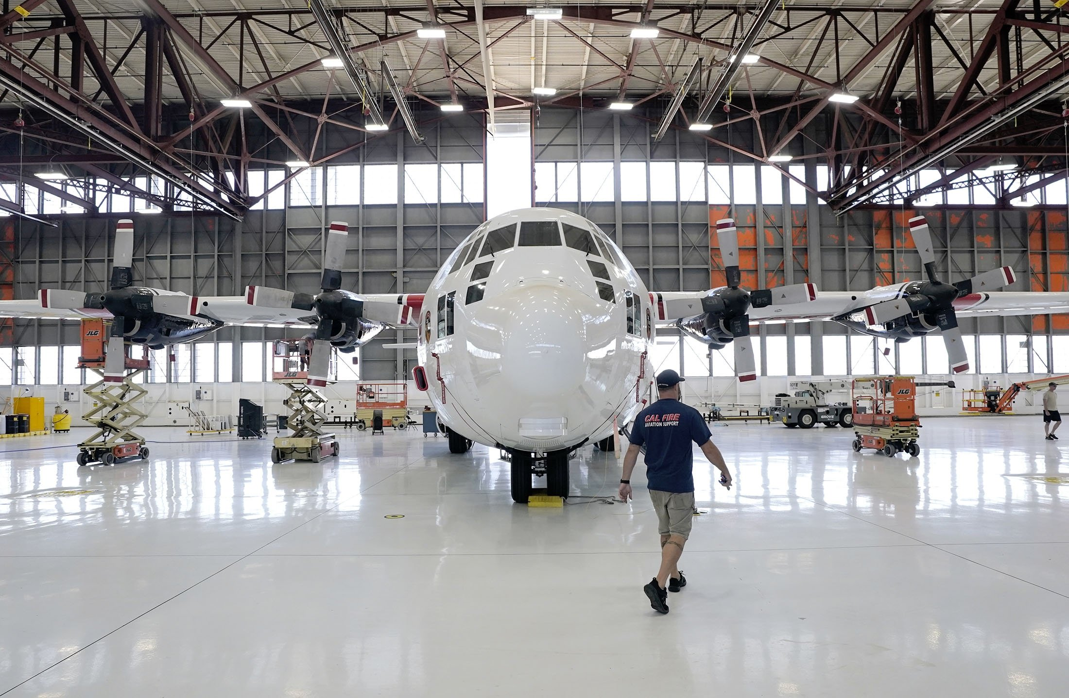Aircraft Mechanic Cody Poole walks past one of the recently acquired C-130 aircraft, hangared at McClellan Airpark in Sacramento, California, U.S., July 23, 2021. (AP Photo)
