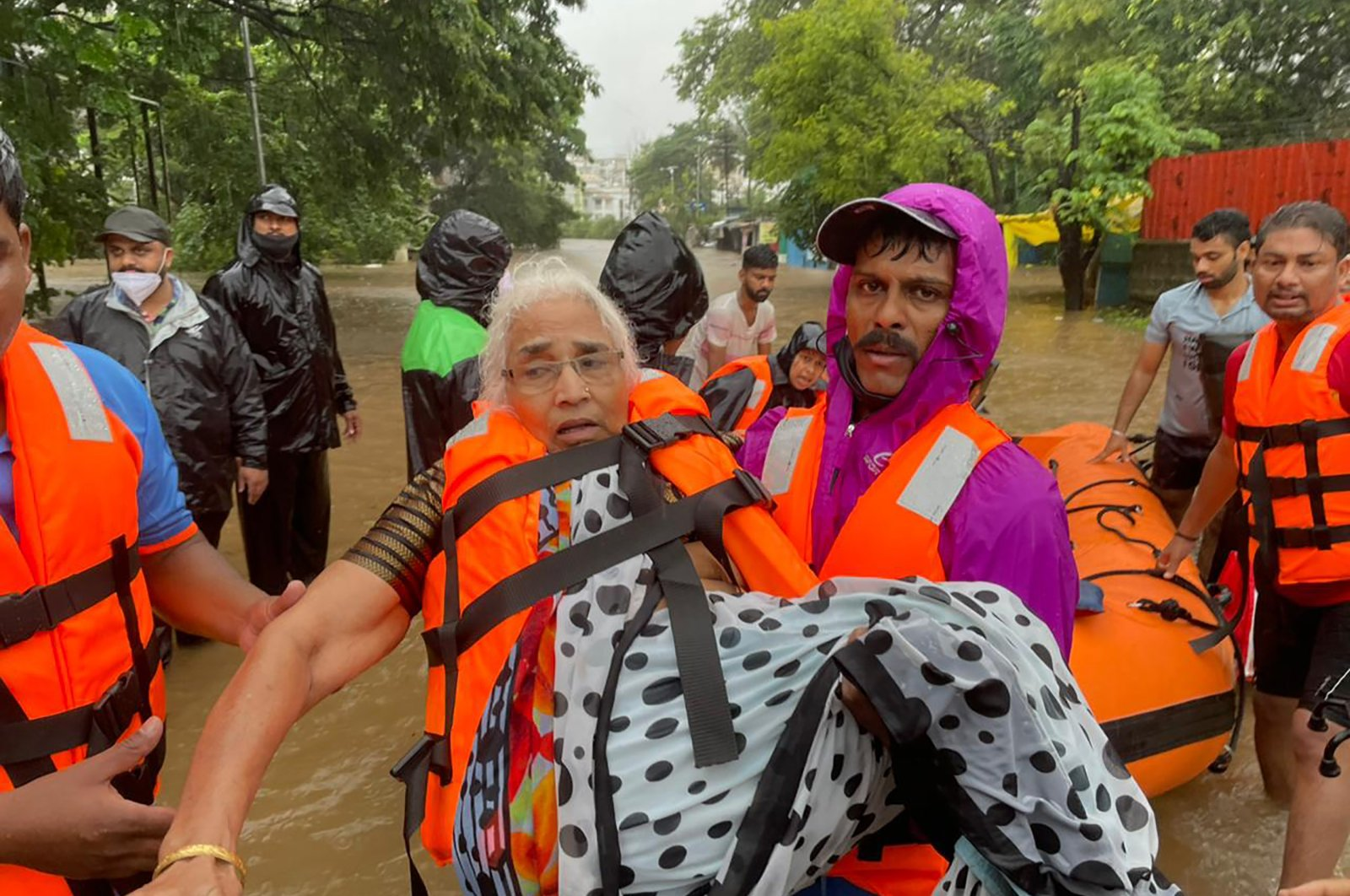 A National Disaster Response Force personnel rescues an elderly woman stranded in floodwaters in Kolhapur, India, July 23, 2021. (AP Photo)
