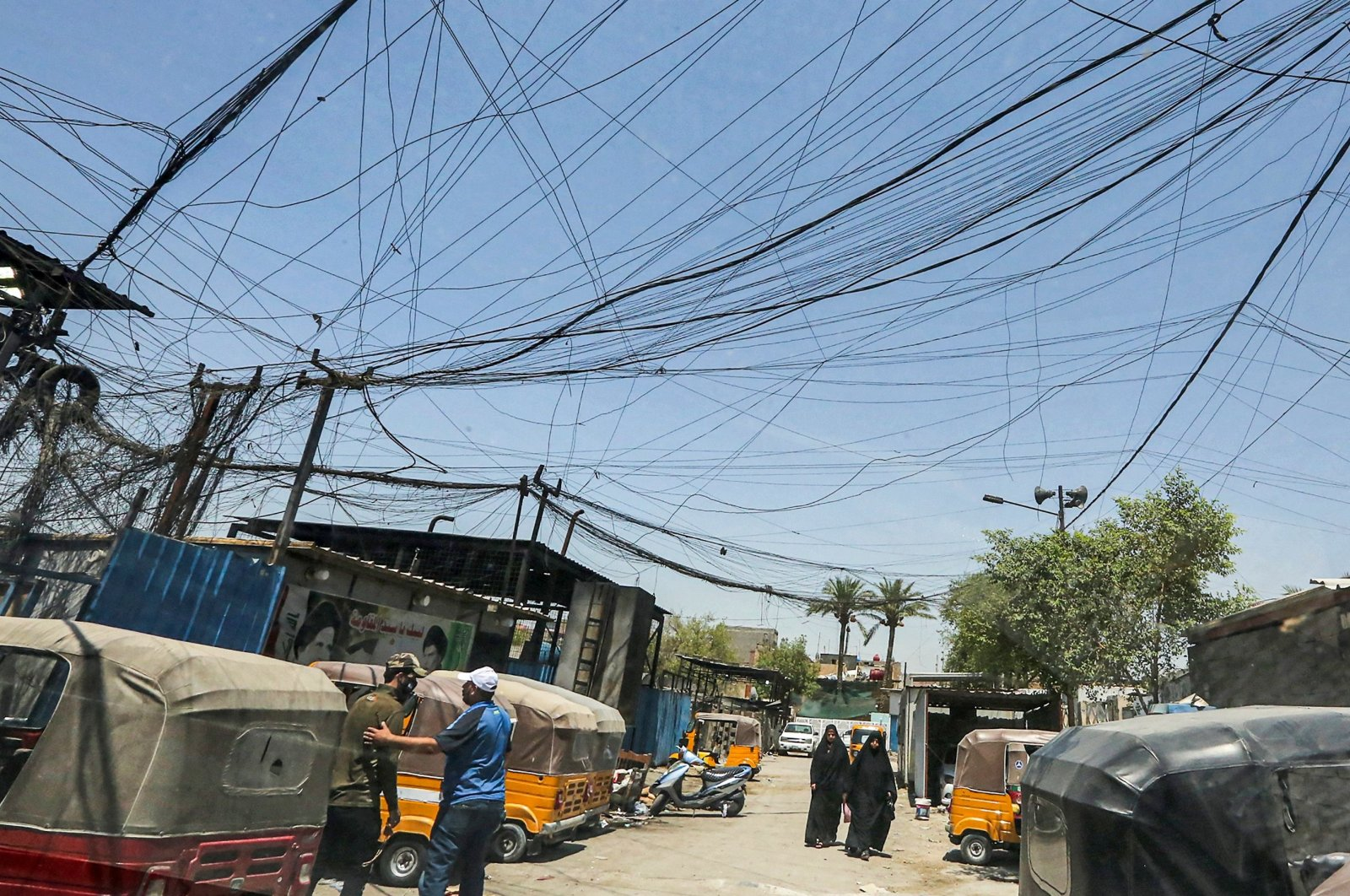 Iraqis walk under cables of private electric generator providers in Sadr City district, Baghdad, Iraq, July 16, 2021. (AFP Photo)