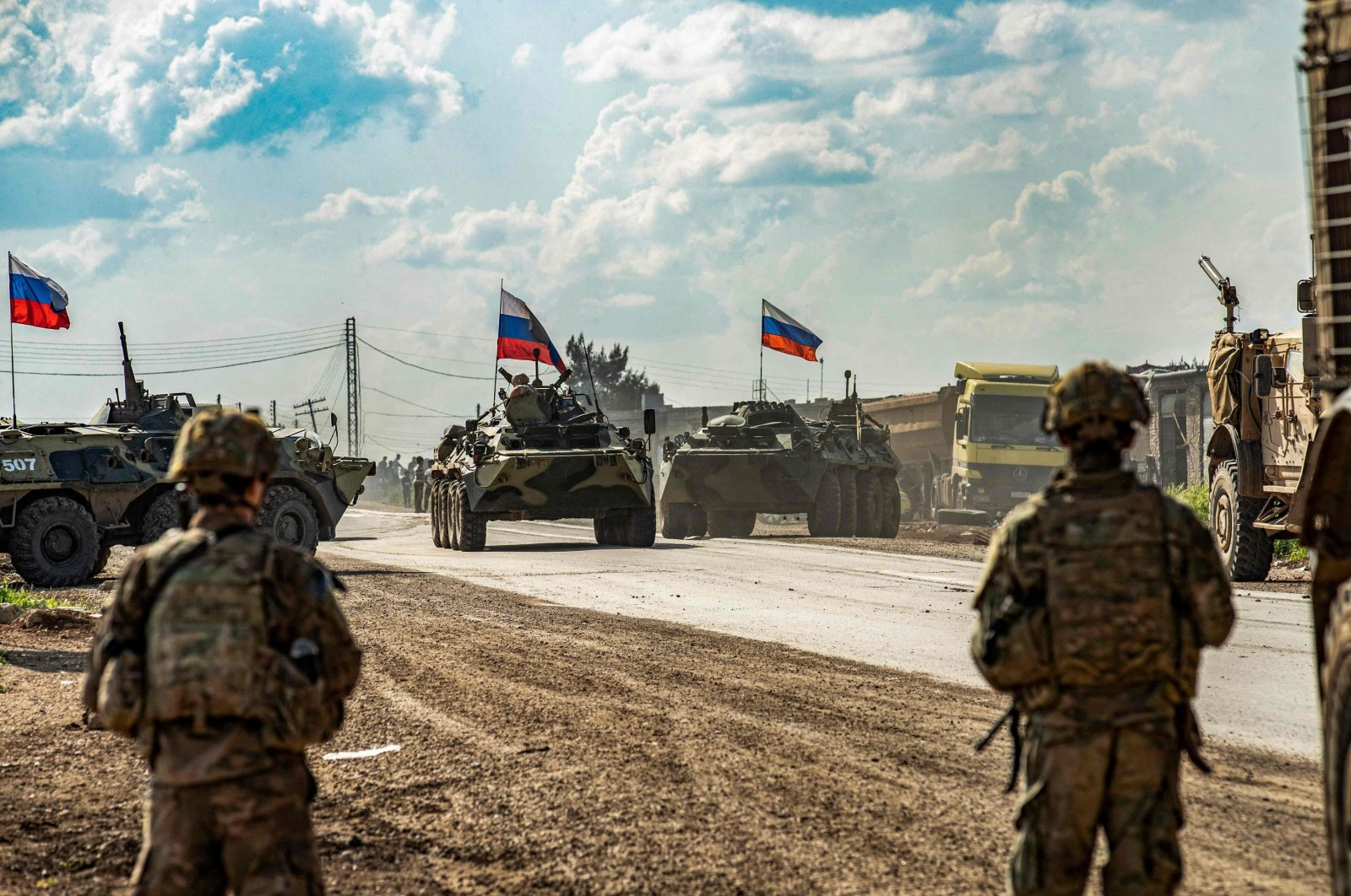 U.S. soldiers stand along a road across from Russian military armored personnel carriers (APCs), near the village of Tannuriyah in the countryside east of Qamishli, northeastern Hasakah province, Syria, on May 2, 2020. (AFP Photo)