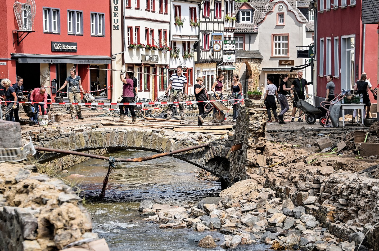 Residents clear debris out of the way after heavy flooding of the Erft River caused severe destruction in the village of Bad Muenstereifel, Euskirchen district, Germany, July 20, 2021. (EPA Photo)