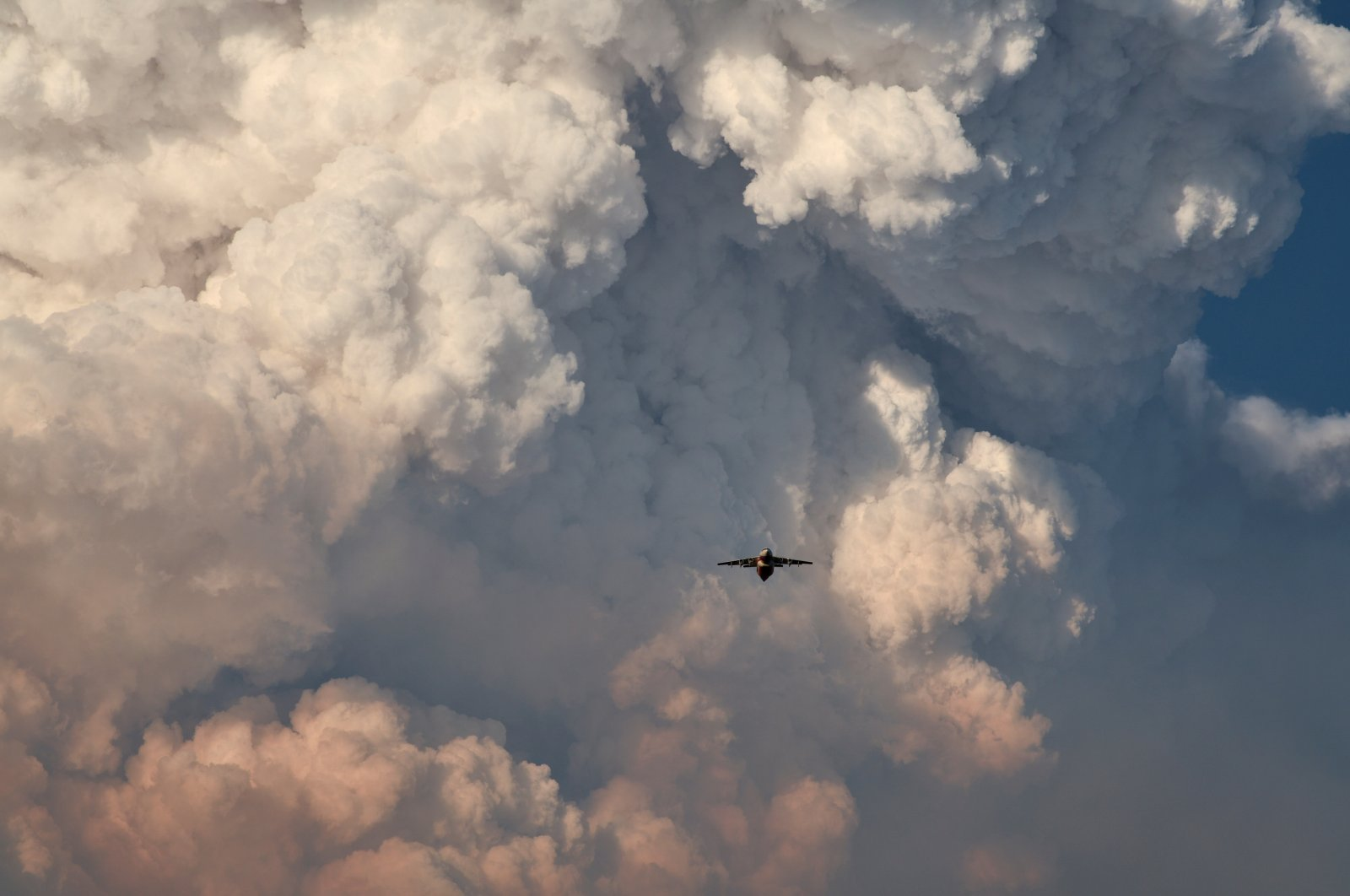 A firefighting aircraft returns to base amid massive plumes of smoke after dropping flame-retarding chemicals on the Bootleg Fire, as it expands to over 225,000 acres, in Bly, Oregon, U.S., July 15, 2021. (Reuters Photo)
