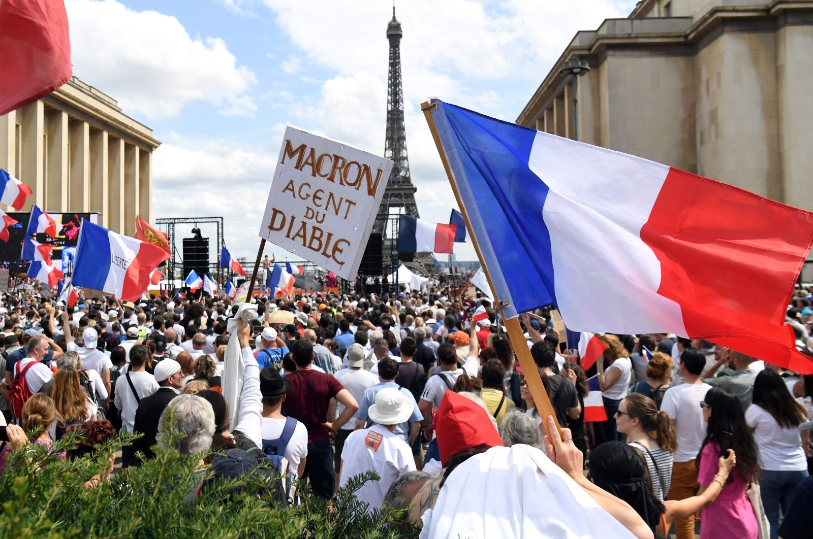 """Protesters hold flags and placards during a protest against the compulsory vaccination for certain workers and the mandatory use of the health pass called for by the French government, on the """"Droits de l'homme"""" (human rights) esplanade at the Trocadero Square, Paris, France, July 24, 2021. (AFP Photo)"""