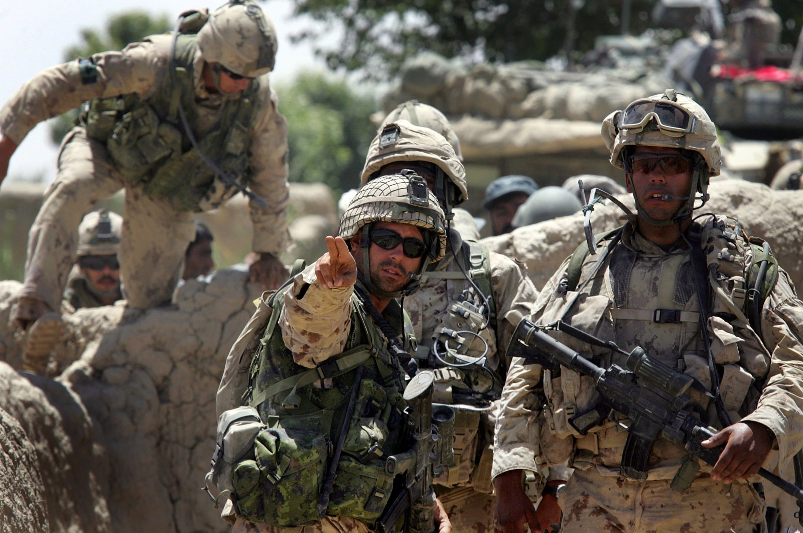 Canadian forces, including Sgt. Dave Limon (C) and Capt. Hugh Atwell (R), prepare to move through a village while conducting a search operation in the Panjwai district about 30 kilometers southwest of Kandahar, Afghanistan, June 13, 2006. (Getty Images)