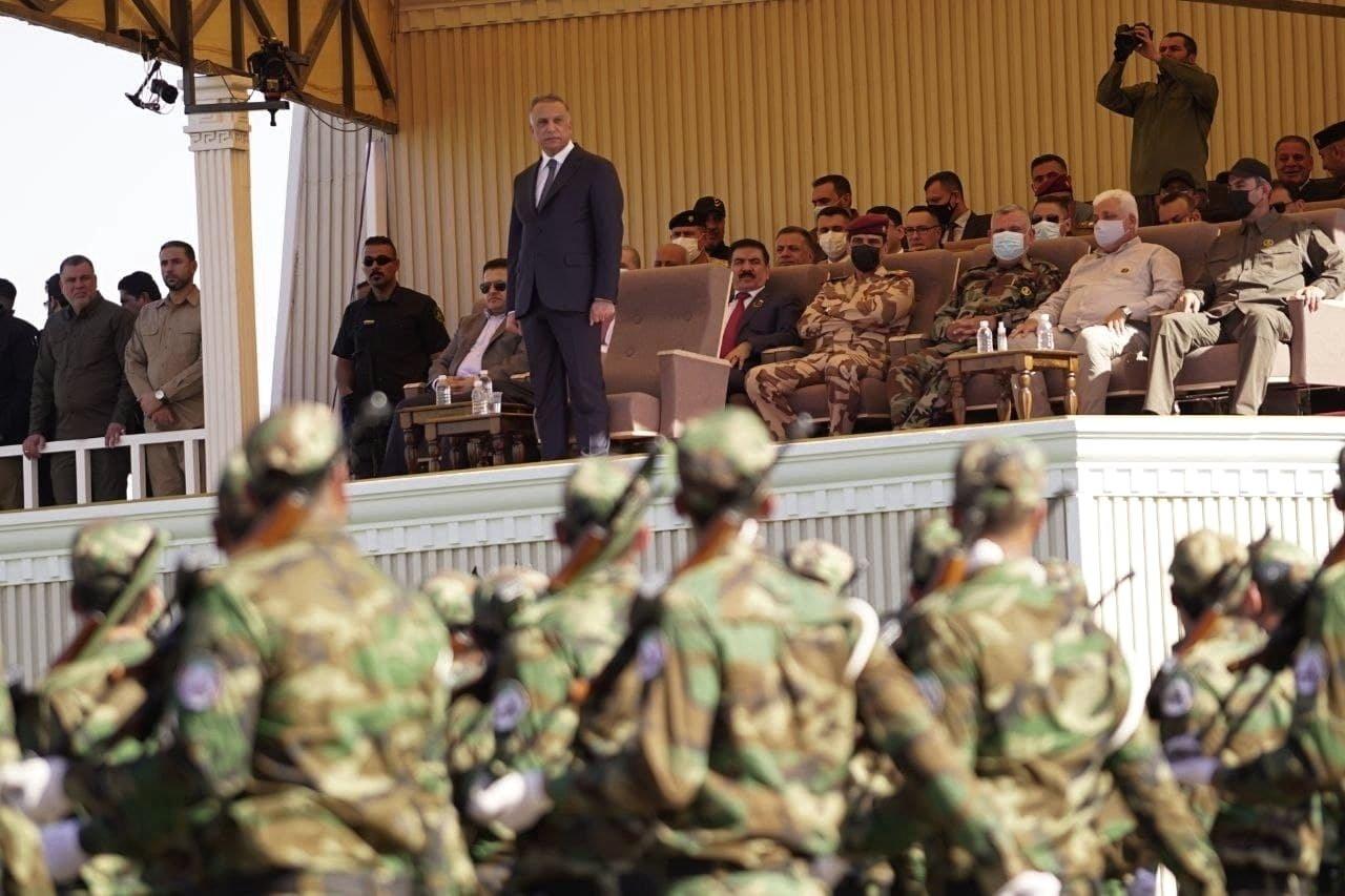 Iraqi Prime Minister Mustafa al-Kadhimi (C) stands while popular Mobilization Forces parade in Diyala, Iraq, June 26, 2021. (AP Photo)