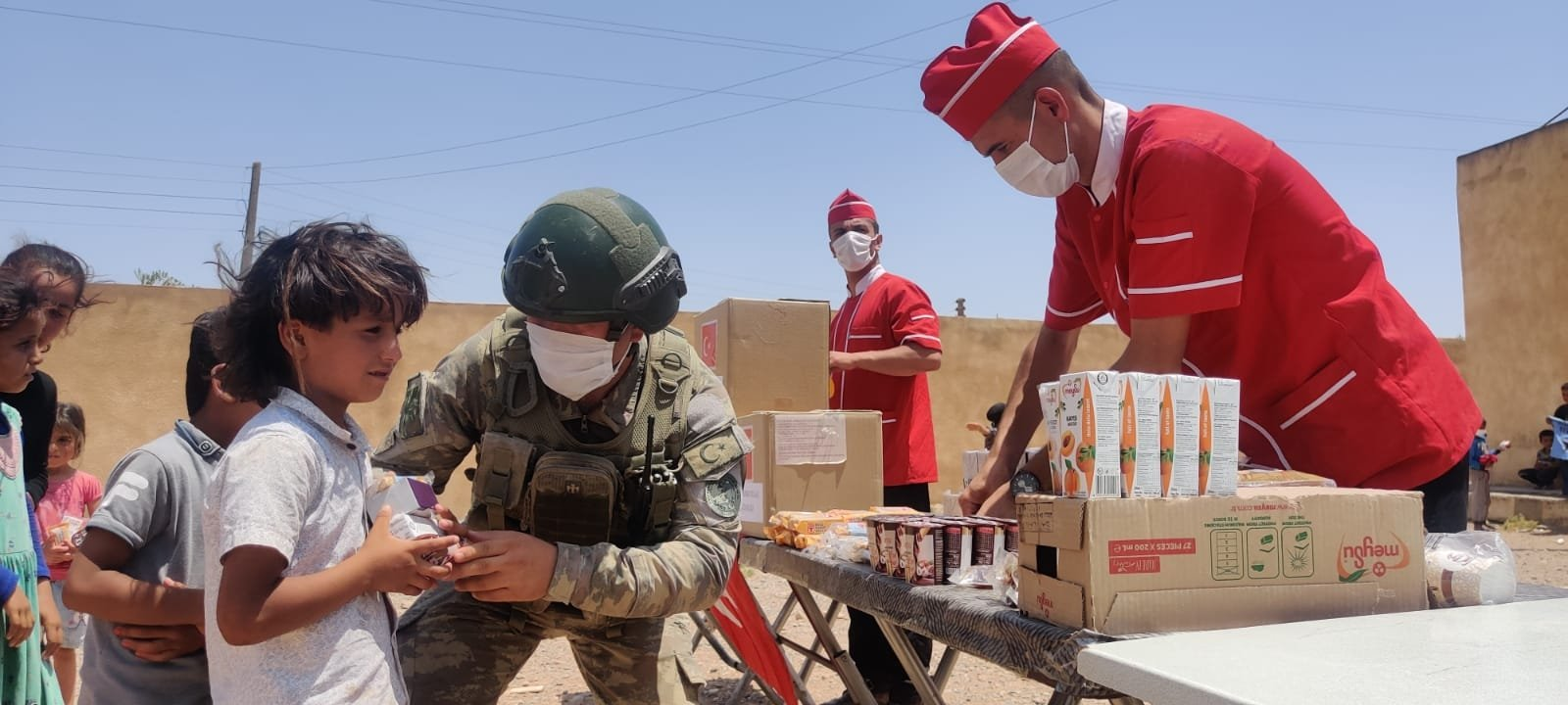 Turkish soldiers distribute aid to civilians in northern Syria's Operation Peace Spring zone, July 24, 2021. (AA Photo)