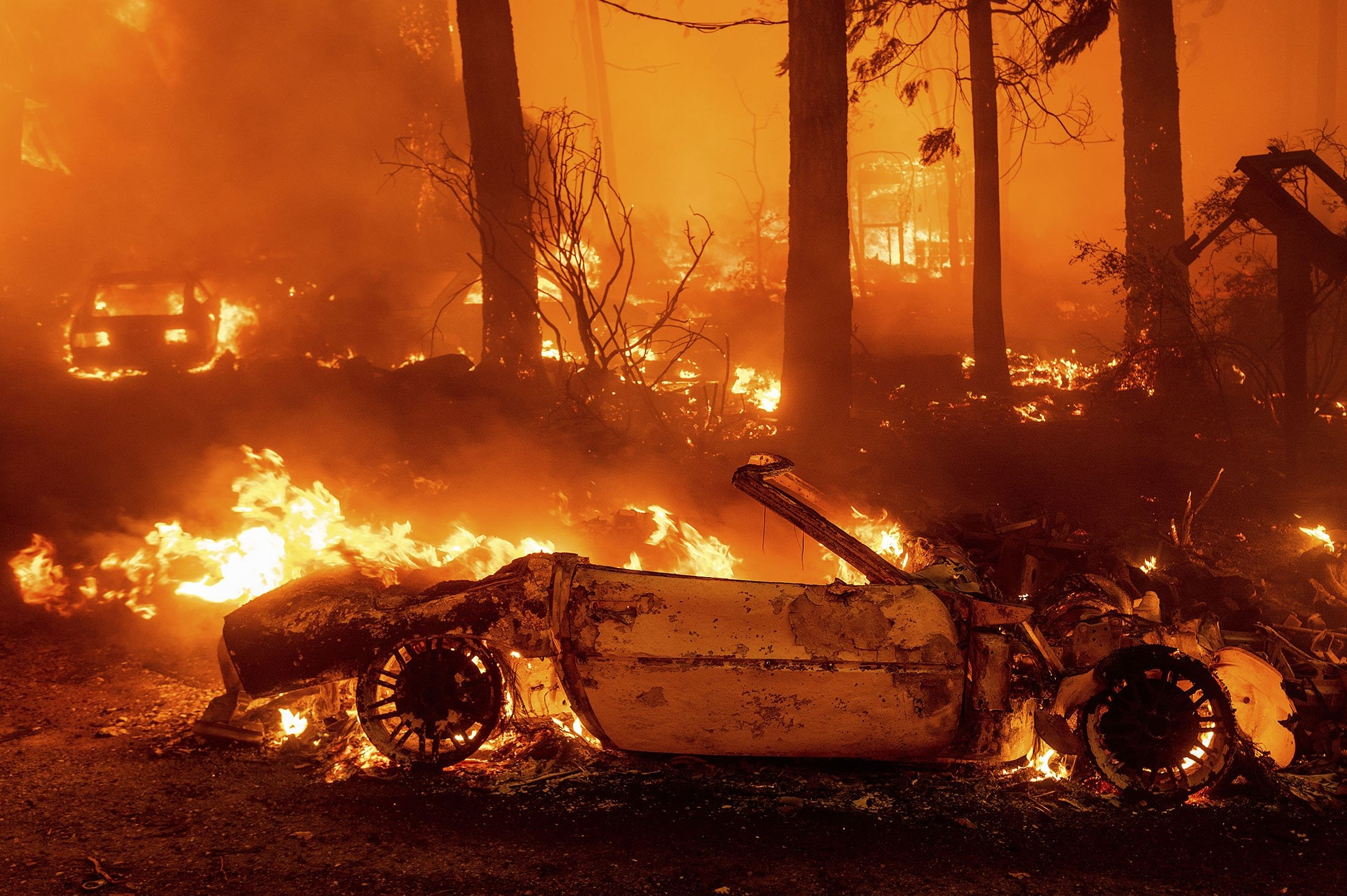 Flames consume vehicles as the Dixie Fire tears through the Indian Falls community in Plumas County, California, U.S., July 24, 2021. (AP Photo)