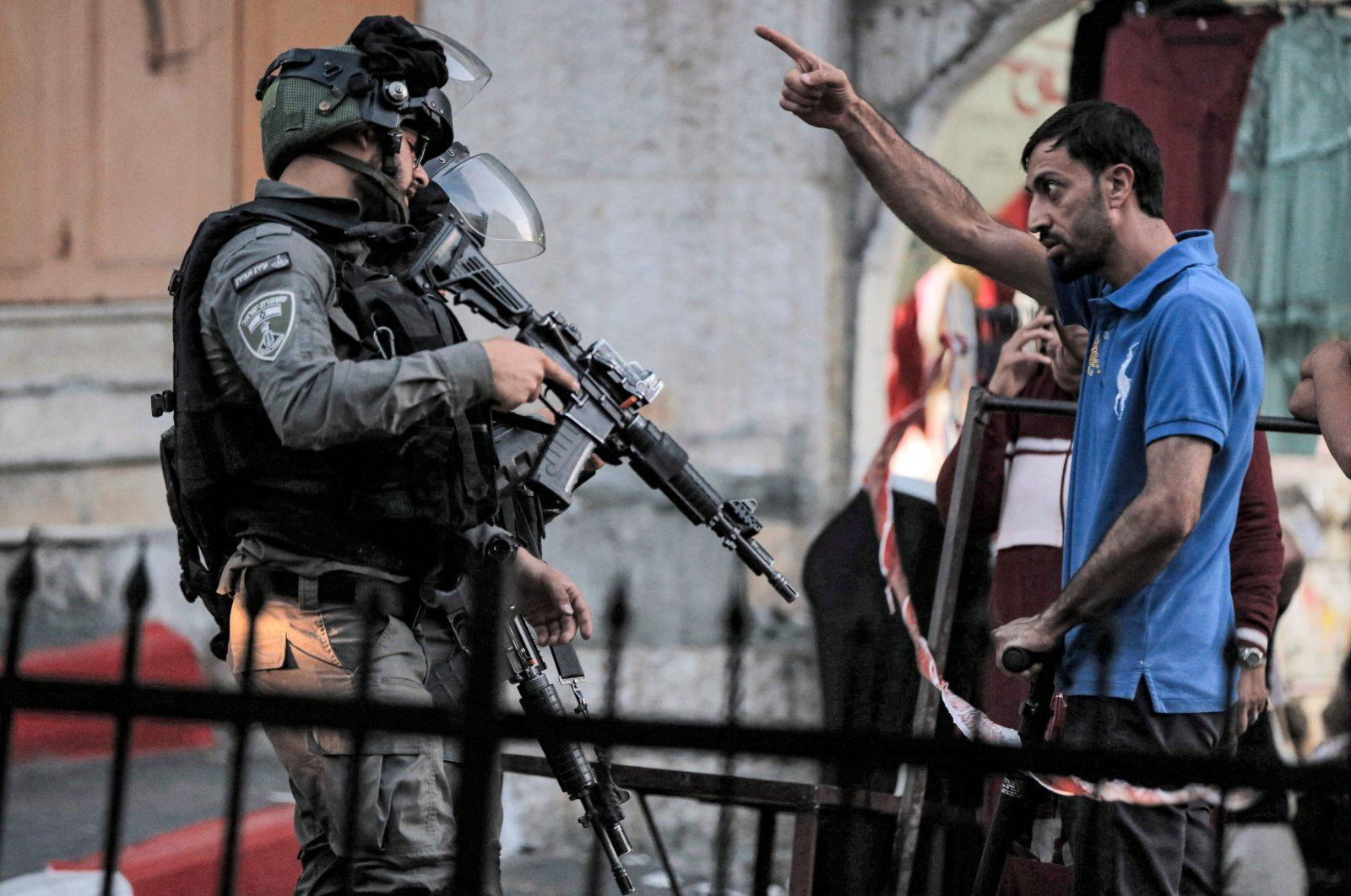A Palestinian man argues with Israeli border guards blocking a street for a procession of Israelis on Tisha B'Av marching towards the shrine of Atnaeil Ben Kinaz in the flashpoint city of Hebron in the occupied West Bank, Palestine, June 18, 2021. (AFP Photo)