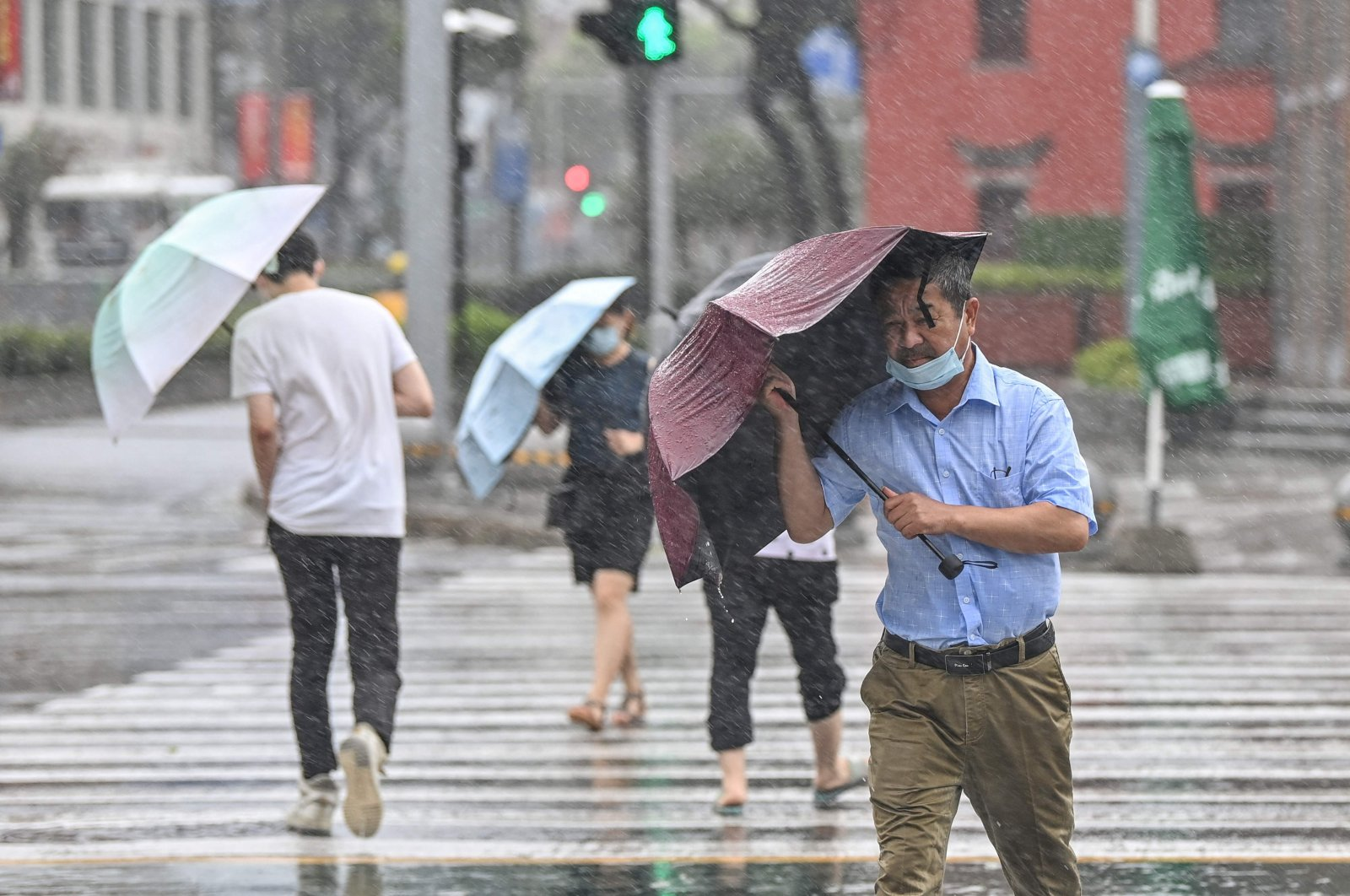 People cross the street in the wind and rain as Typhoon In-fa lashes the country's eastern coast, Ningbo, China, July 25, 2021. (AFP Photo)