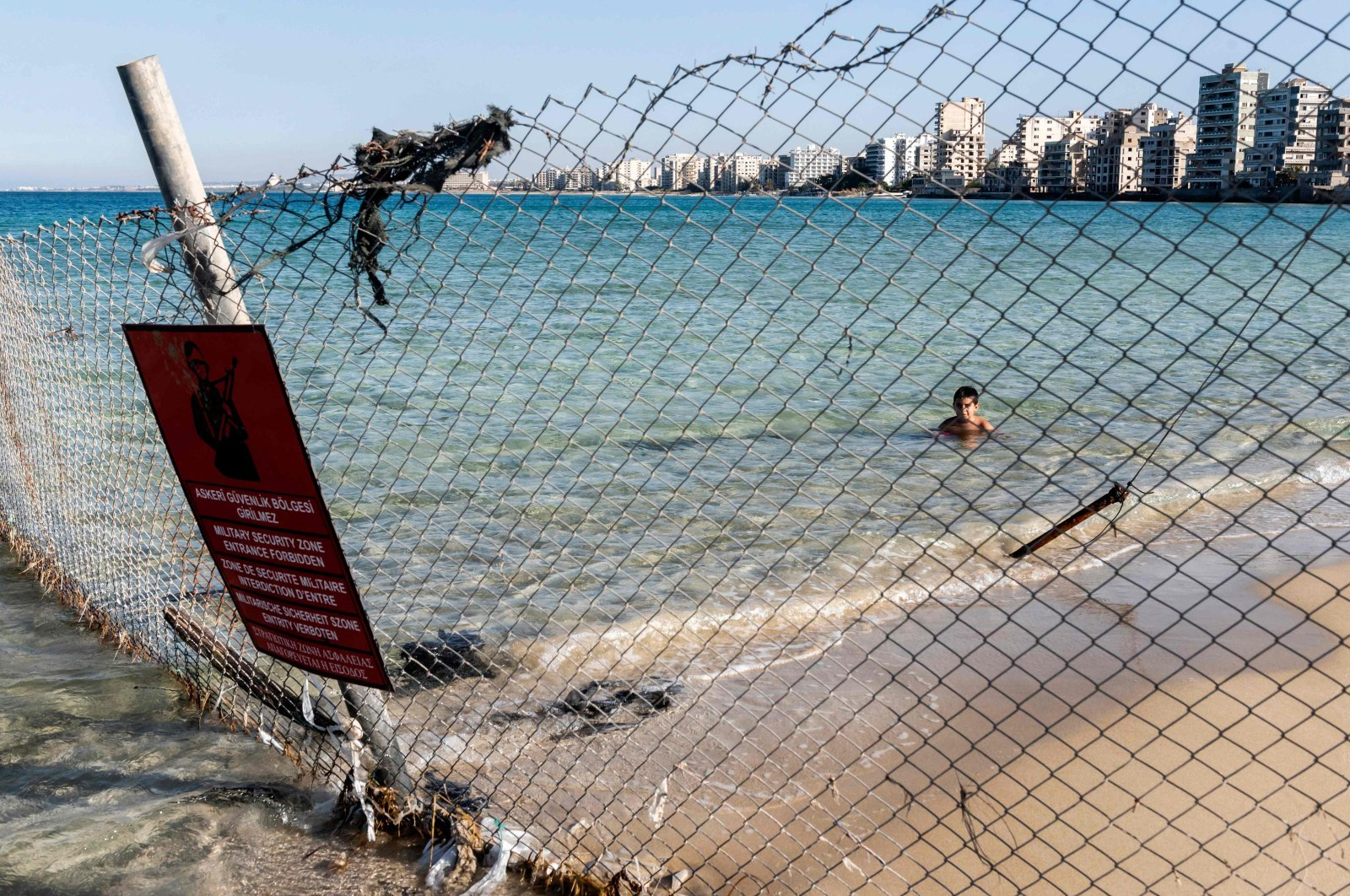 A child swims behind a Turkish army sign in the fenced-off area of Varosha (Maraş) in Famagusta town, Turkish Republic of Northern Cyprus (TRNC), June 19, 2021. (AFP Photo)