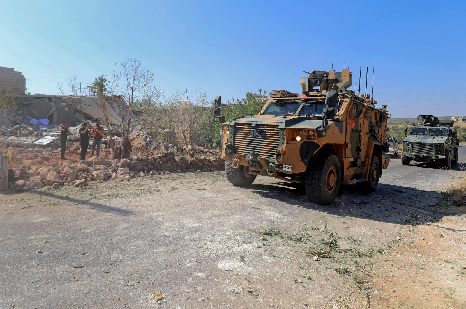 Turkish troops in armored personnel carriers arrive at the scene of a reported regime artillery shelling, in the village of Iblin in the Jabal al-Zawiya region of Syria's opposition-held northwestern Idlib province, July 22, 2021. (AFP Photo)