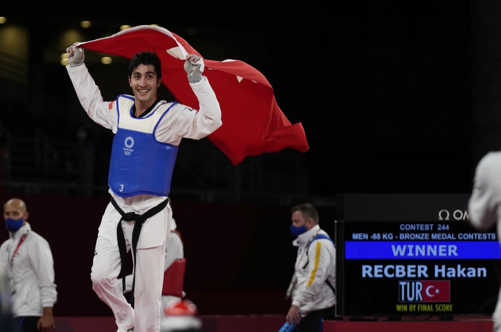 Turkey's Hakan Reçber celebrates with the national flag after winning bronze in the taekwondo men's 68-kilogram match at the Tokyo 2020 Olympics, Tokyo, Japan, July 25, 2021. (AP Photo)