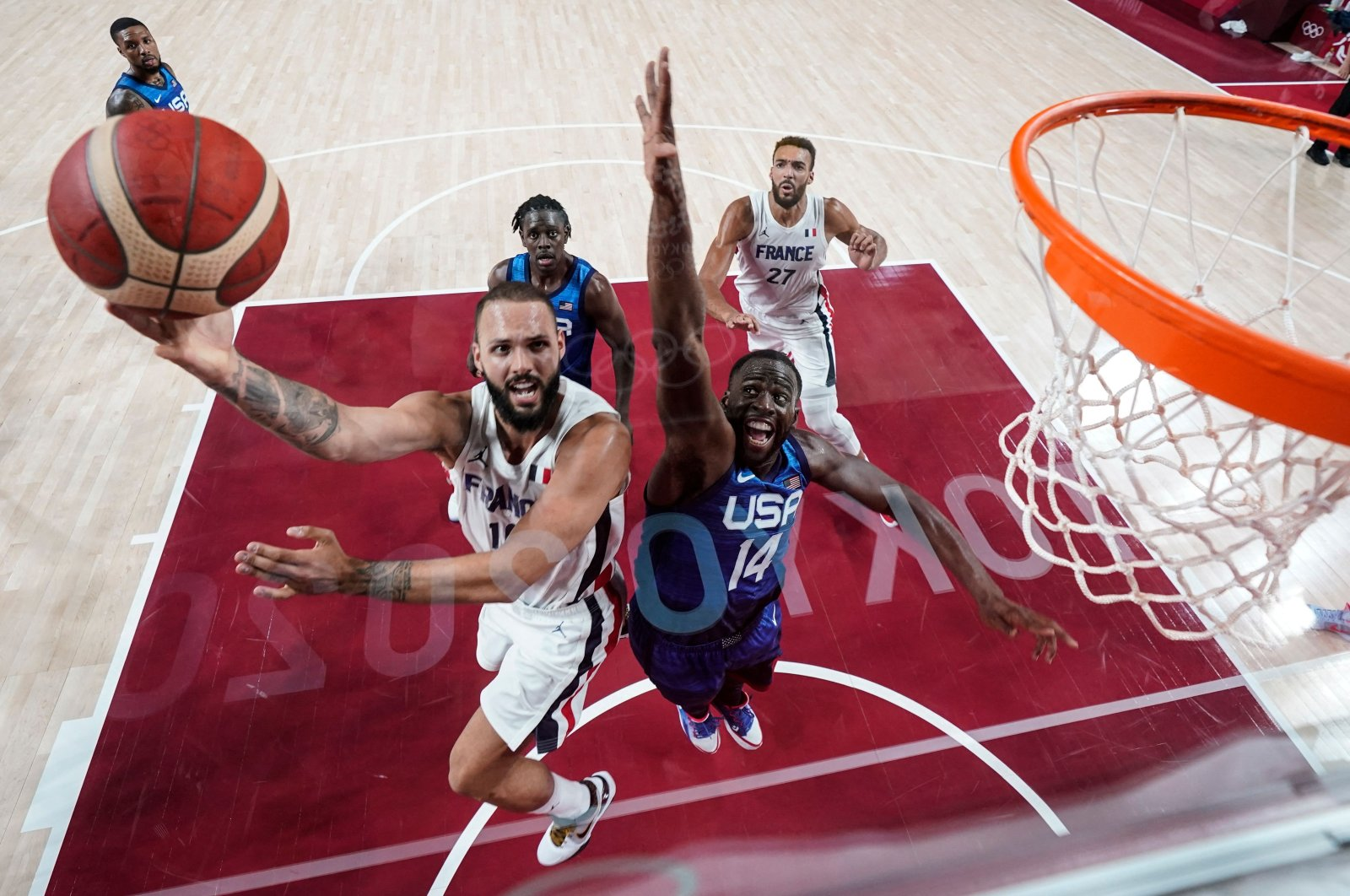 France's Evan Fournier (L) goes for the basket past the U.S.'s Draymond Jamal Green during the Tokyo 2020 Olympic Games men's preliminary round Group A match at the Saitama Super Arena, Saitama, Japan, July 25, 2021. (AFP Photo)