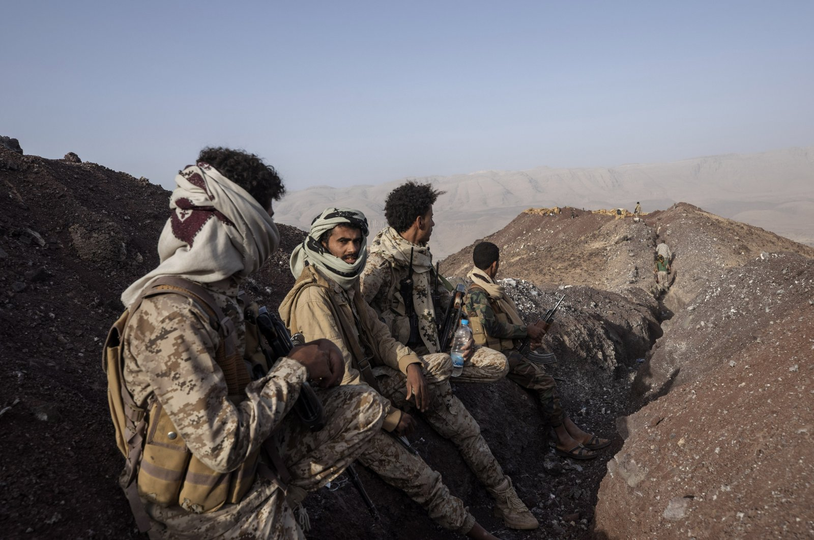 Yemeni fighters backed by the Saudi-led coalition stand at a distance from the front line after clashes with Houthi rebels on the Kassara front line near Marib, Yemen, June 20, 2021. (AP Photo)