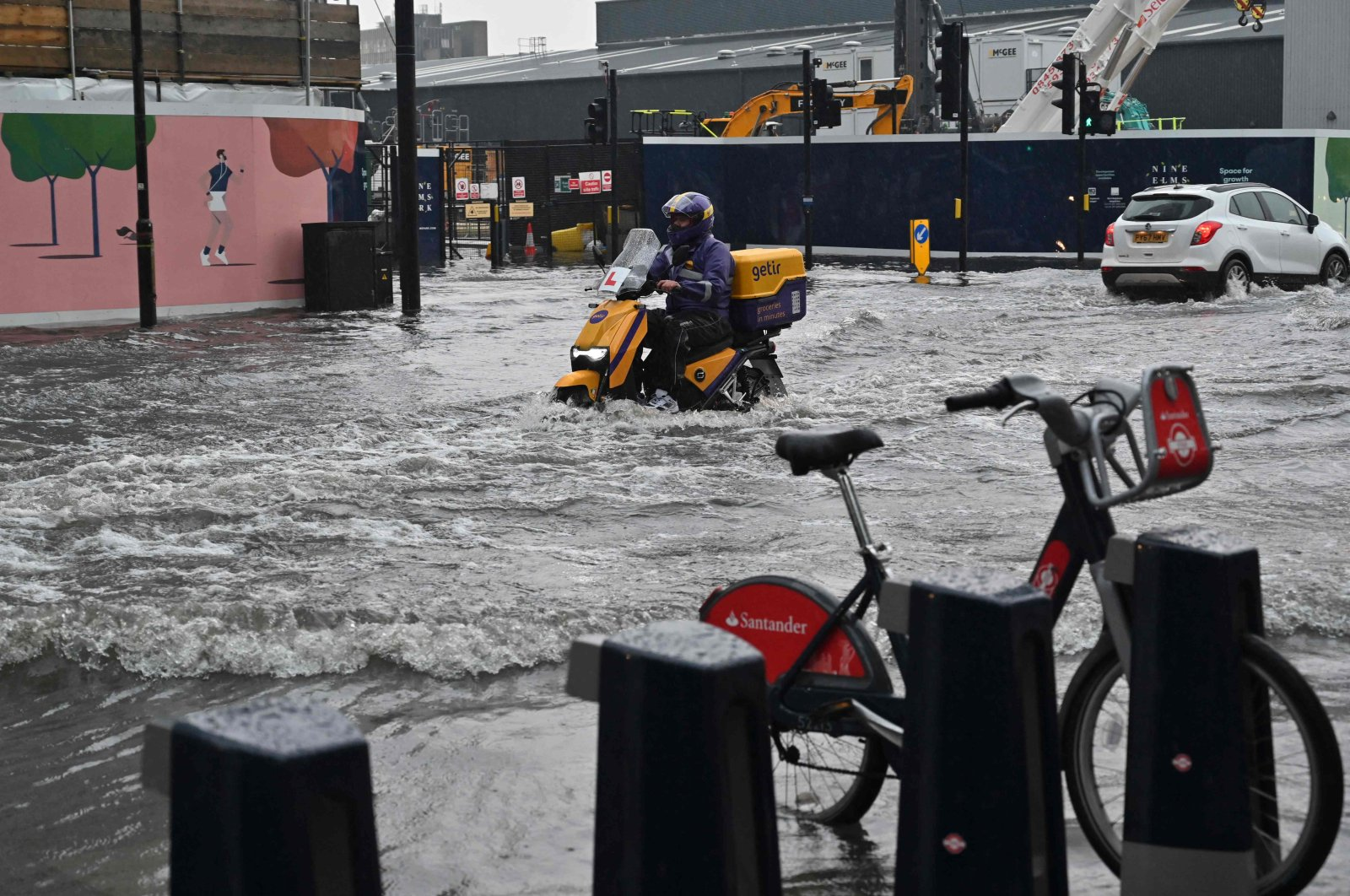 A motorcyclist rides through deep water on a flooded road in The Nine Elms district of London, England, July 25, 2021. (AFP Photo)