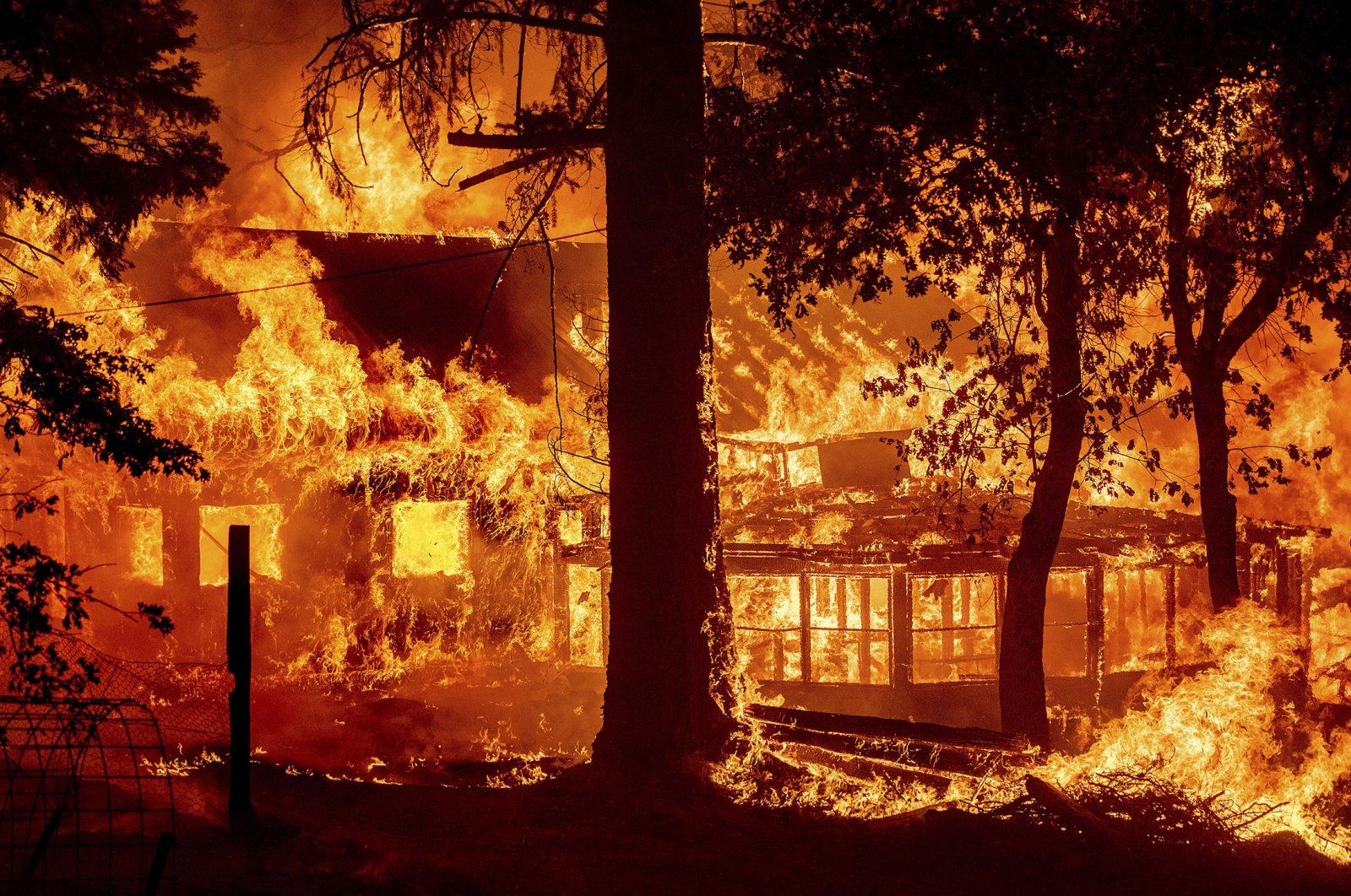 Flames from the Dixie Fire consume a home in the Indian Falls community of Plumas County, California, U.S., July 24, 2021. (AP Photo)