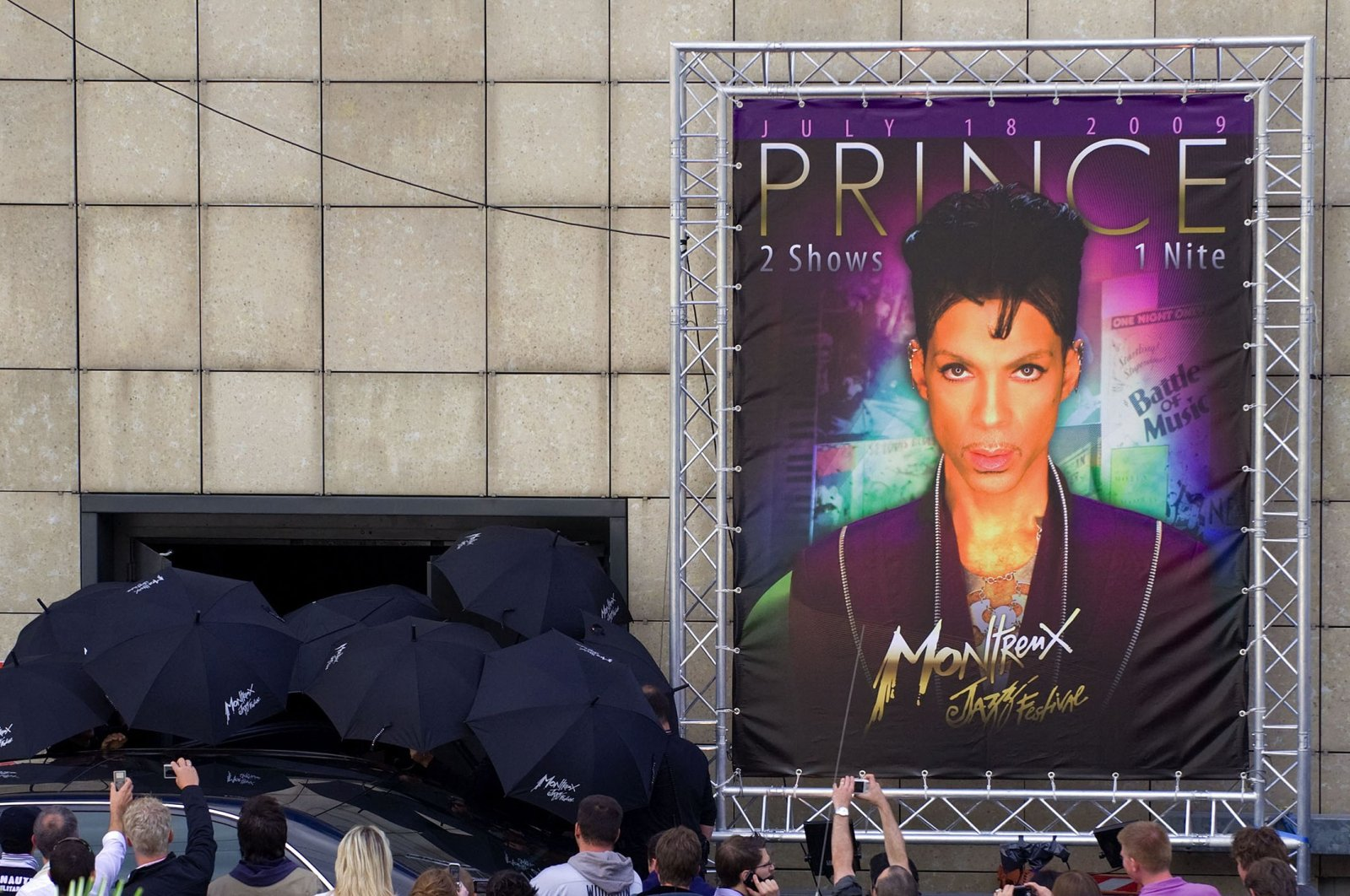 Security staff hold umbrellas to hide U.S. singer Prince close to a giant poster of the entertainer as the pop maverick leaves the Auditorium after his sound check in Lausanne, Switzerland, July 18, 2009. (AFP Photo)