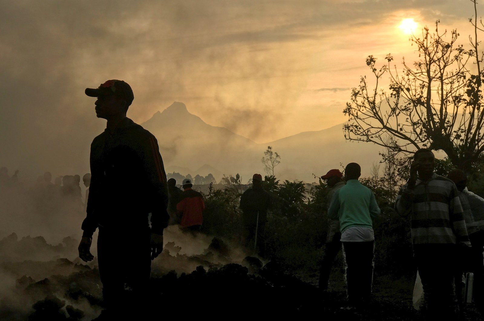 Residents walk near destroyed homes with the smoldering lava deposited by the eruption of Mount Nyiragongo volcano, DR Congo. (Reuters Photo)