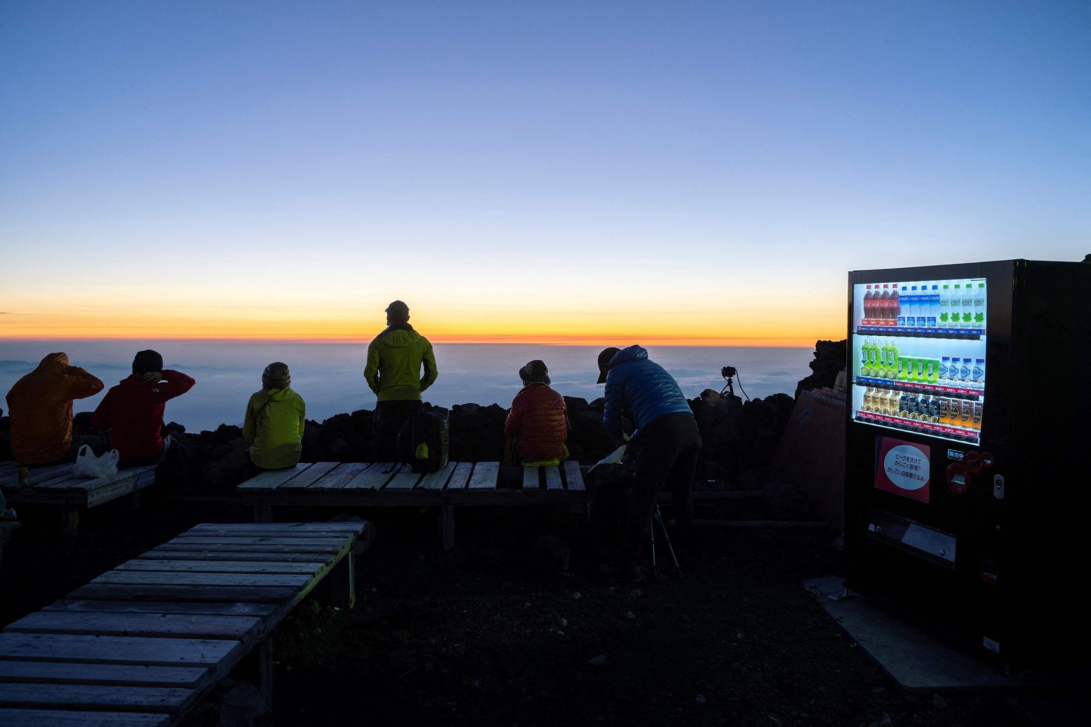 A vending machine with warm and cold drinks for sale can be seen as people wait for the sunrise at the summit of Mount Fuji, some 70 kilometers (43 miles) west of the capital Tokyo, Japan, July 19, 2021. (AFP Photo)