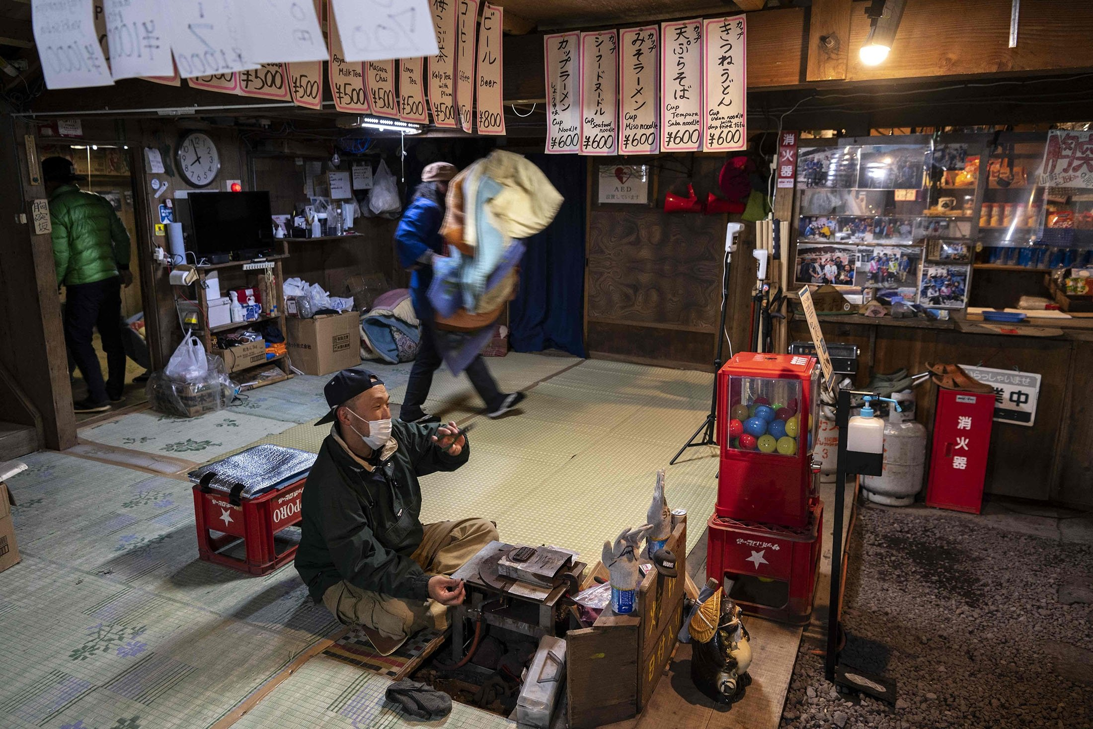 People work inside a hut selling food and other items, near the summit of Mount Fuji, some 70 kilometers (43 miles) west of the capital Tokyo, Japan, July 18, 2021. (AFP Photo)