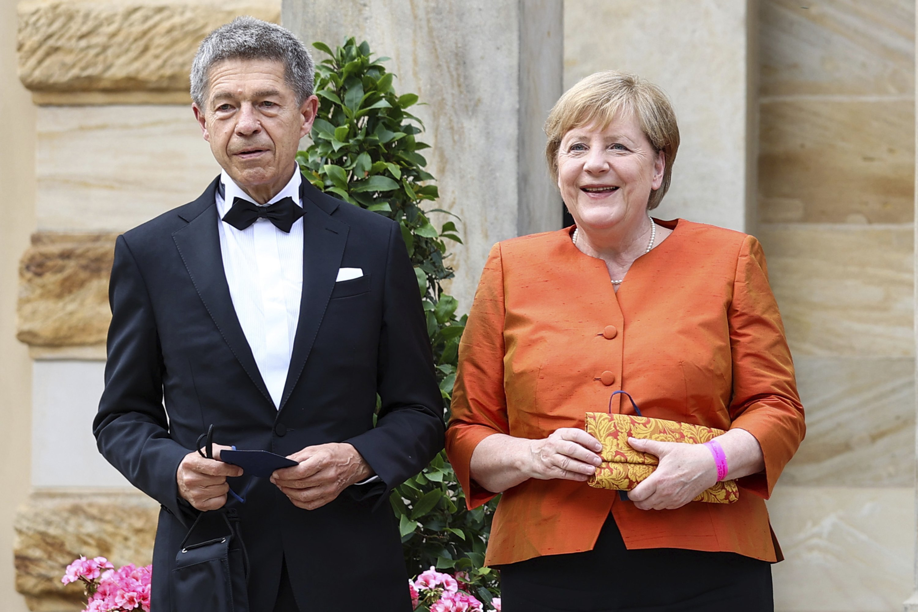German Chancellor Angela Merkel and her husband Joachim Sauer arrive at the festival hall in Bayreuth, Germany, Sunday July 25, 2021.  (AP Photo)
