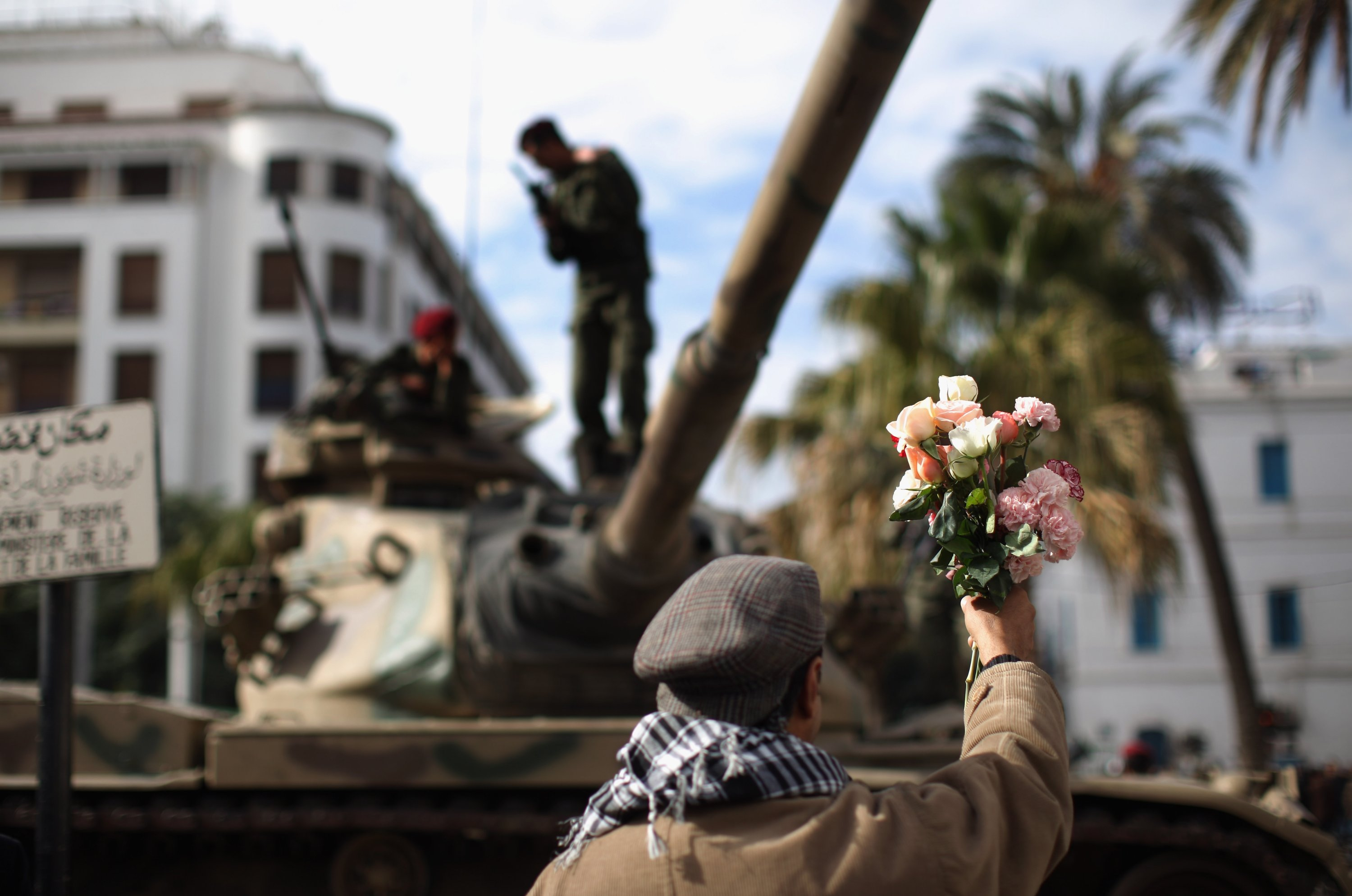A demonstrator offers flowers to soldiers on their tank as an uneasy peace hangs over Tunisia, in Tunis, Tunisia, Jan. 21, 2011. (Photo by Getty Image)