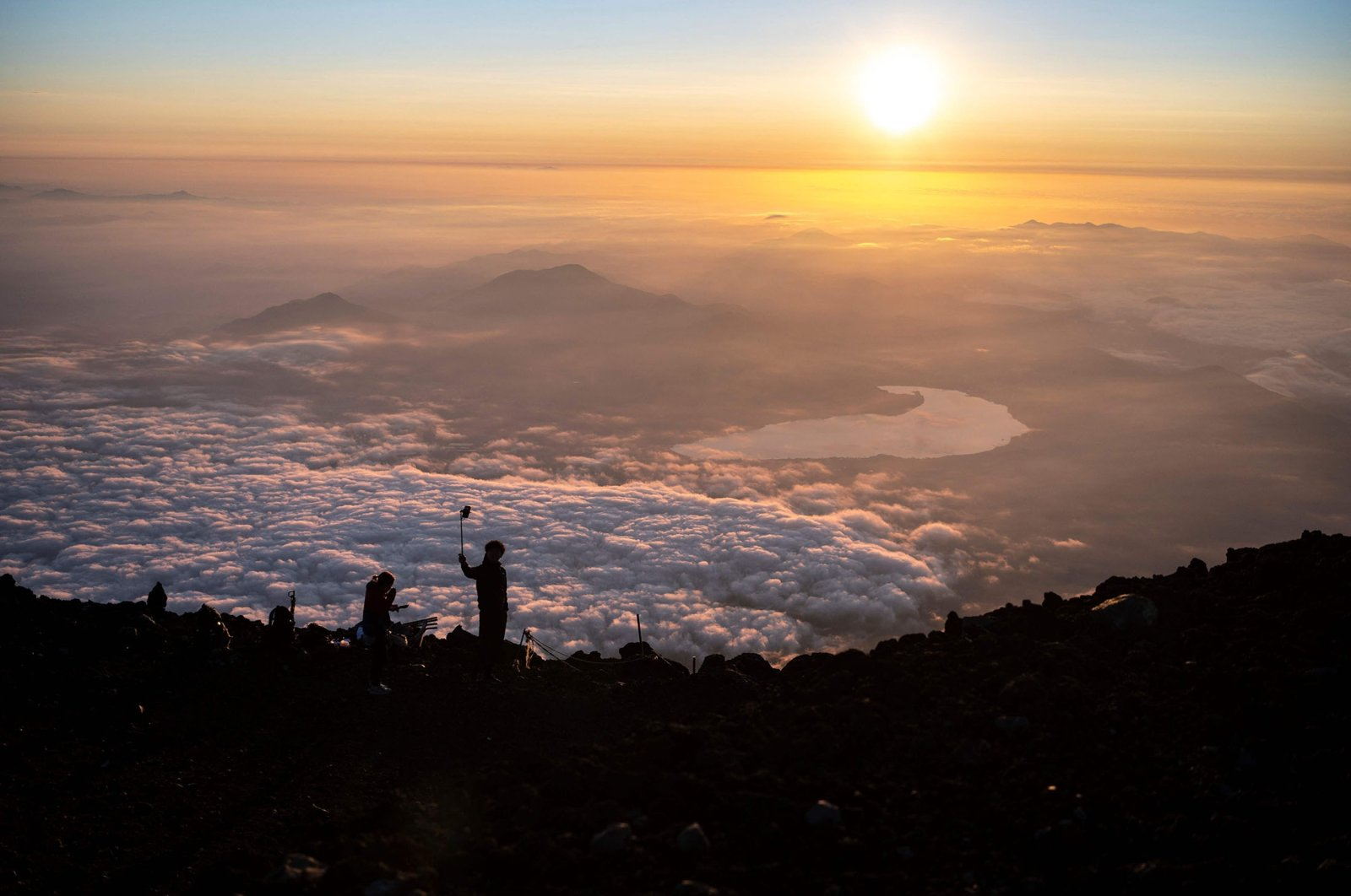 People watch the sunrise from the summit of Mount Fuji, some 70 kilometers (43 miles) west of the capital Tokyo, Japan, July 19, 2021. (AFP Photo)