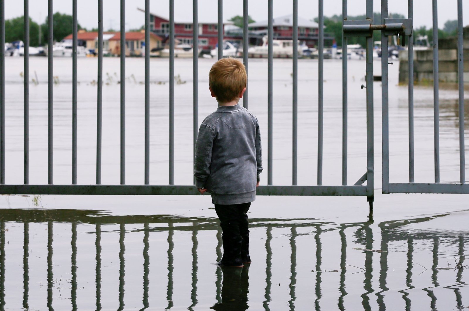 A child looks on as water floods through a fence, in Wessem, the Netherlands, July 16, 2021. (Reuters Photo)