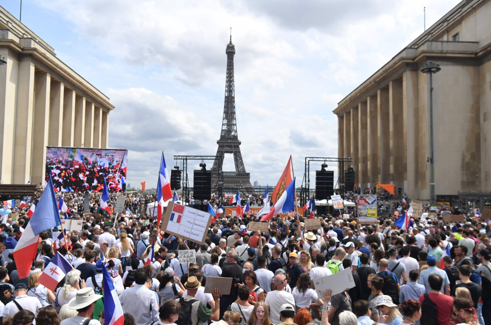 """People take part in a protest against the compulsory vaccination for certain workers and the mandatory use of the health pass called by the French government, on the """"Droits de l'homme"""" (human rights) esplanade at the Trocadero Square, in front of the Eiffel Tower in Paris, France, July 24, 2021. (AFP Photo)"""