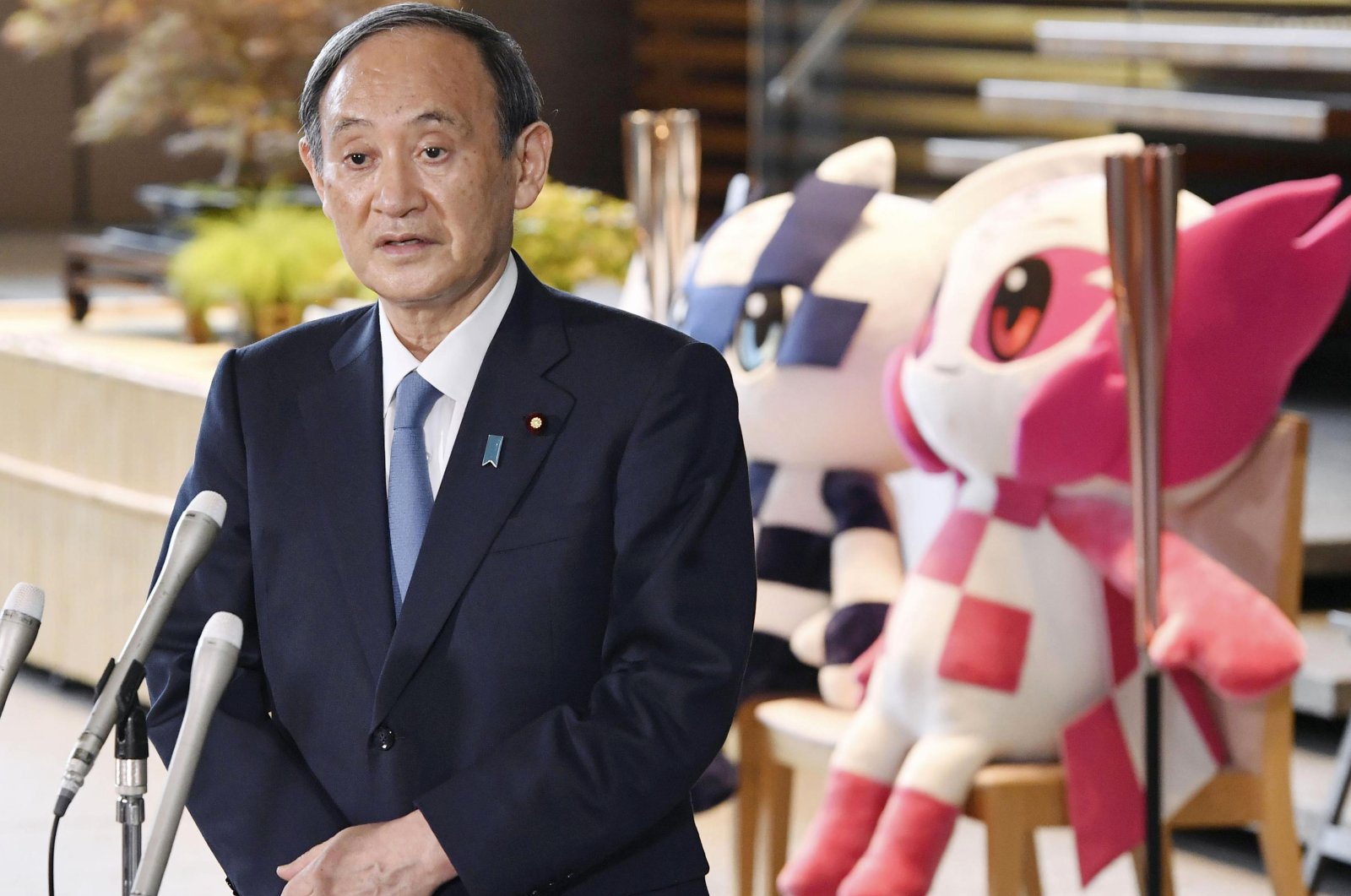 Japan's Prime Minister Yoshihide Suga speaks to the media in front of the Olympics mascots at the prime minister's office in Tokyo, July 1, 2021. (AP Photo)