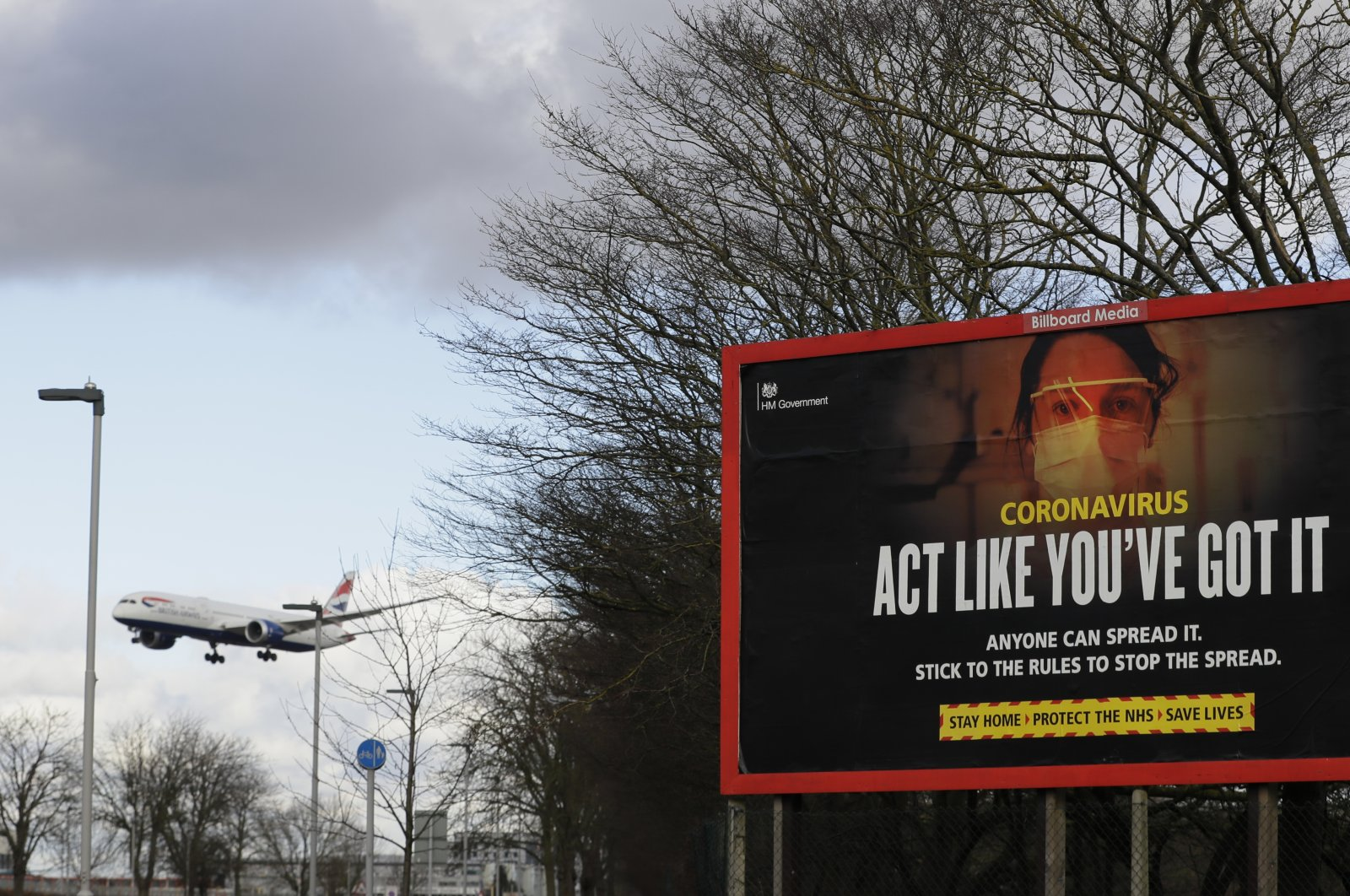 A plane comes in to land near a government coronavirus information sign at Heathrow Airport in London, the U.K., Feb. 5, 2021. (AP Photo)