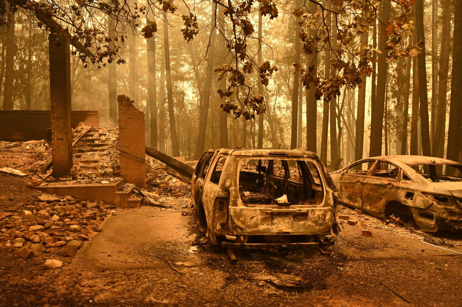 Burned vehicles smolder at a property during the Dixie fire in the Indian Falls area of unincorporated Plumas County, California, U.S., July 25, 2021. (AFP Photo)