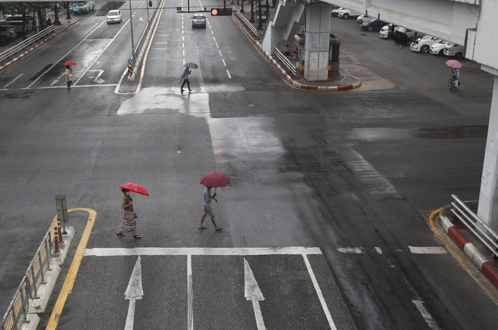 Pedestrians wearing face masks use umbrellas to protect themselves from the rain as they cross a road in downtown Yangon, Myanmar, July 19, 2021. (AP Photo)