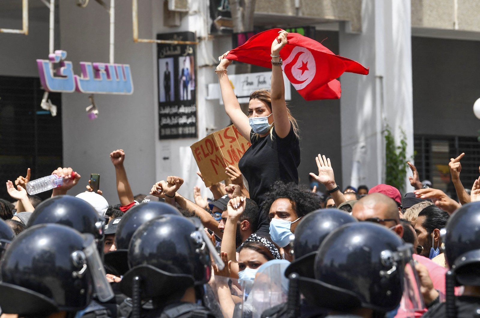 A Tunisian protester lifts a national flag at an anti-government rally as security forces block off the road in front of the Parliament in the capital Tunis on July 25, 2021. (AFP Photo)