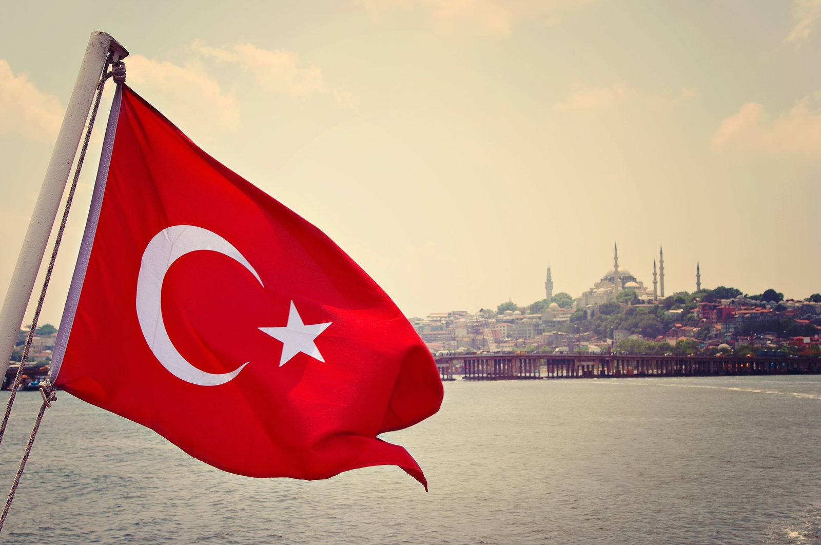 The Turkish flag flaps in the wind in front of the Bosporus and Sultanahmet Camii (Blue Mosque), Istanbul, Turkey. (Shutterstock Photo)